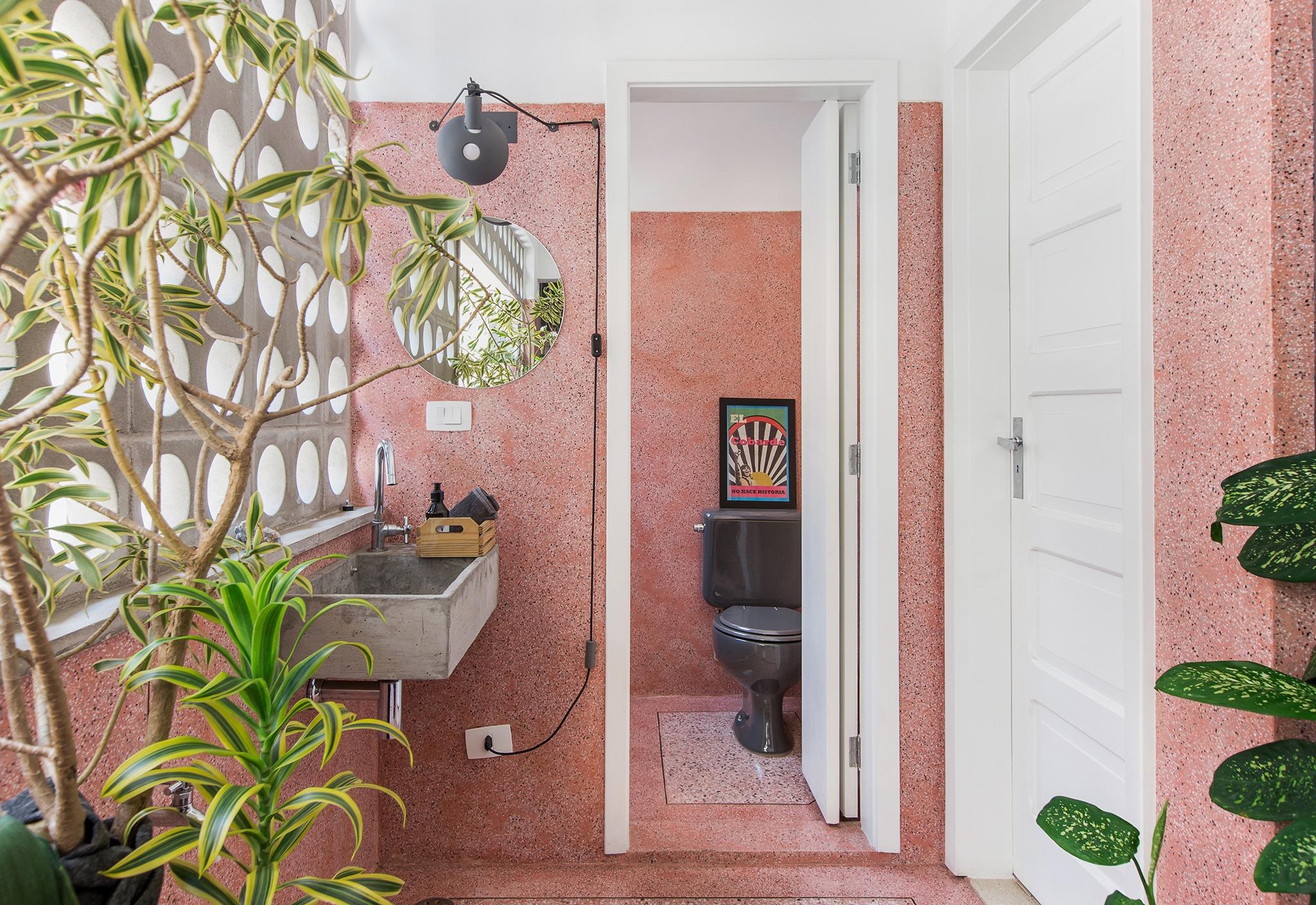 Banheiro com piso e paredes de granilite rosa