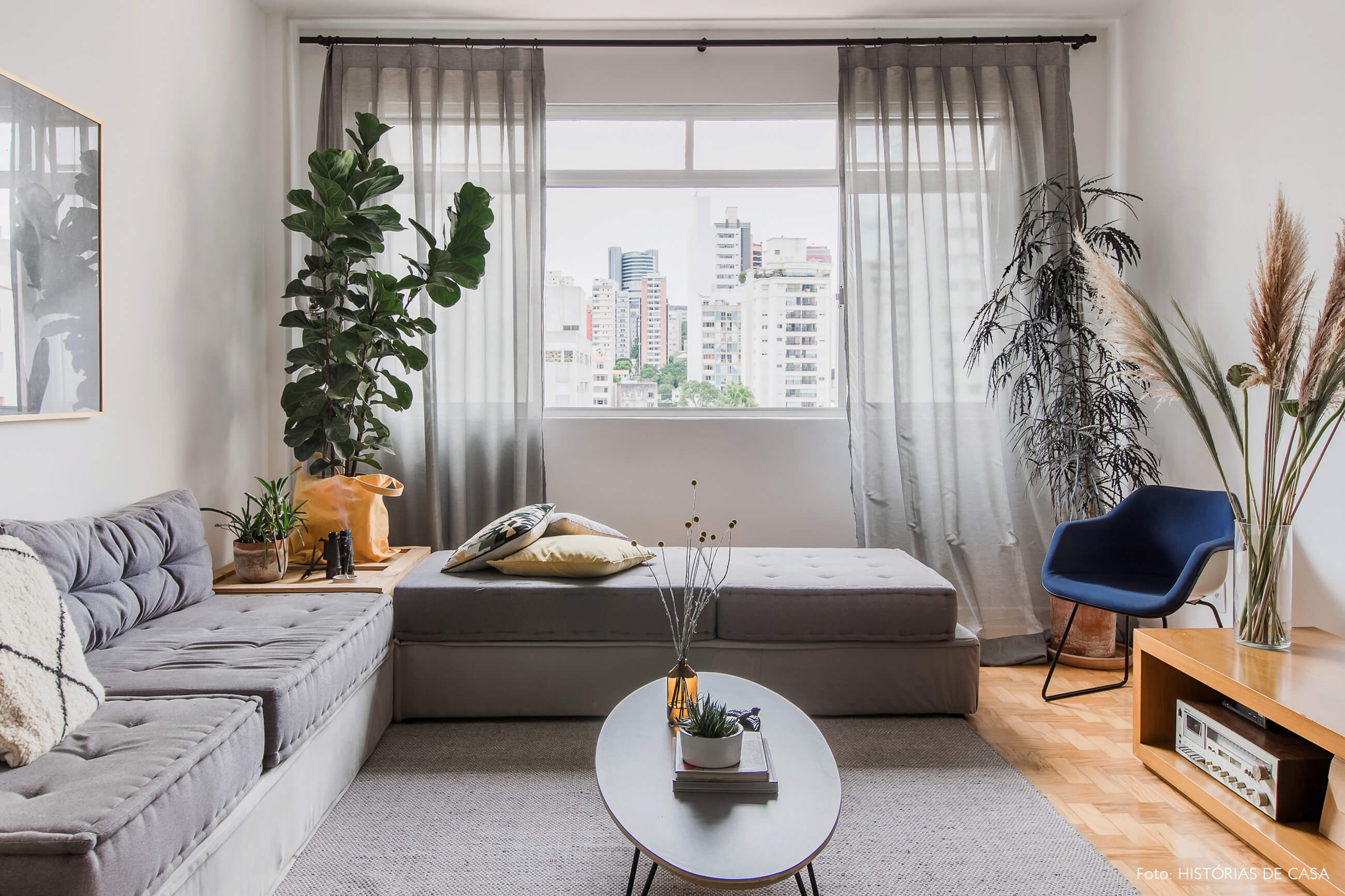 Sala com tons de cinza no sofá, tapete e cortinas