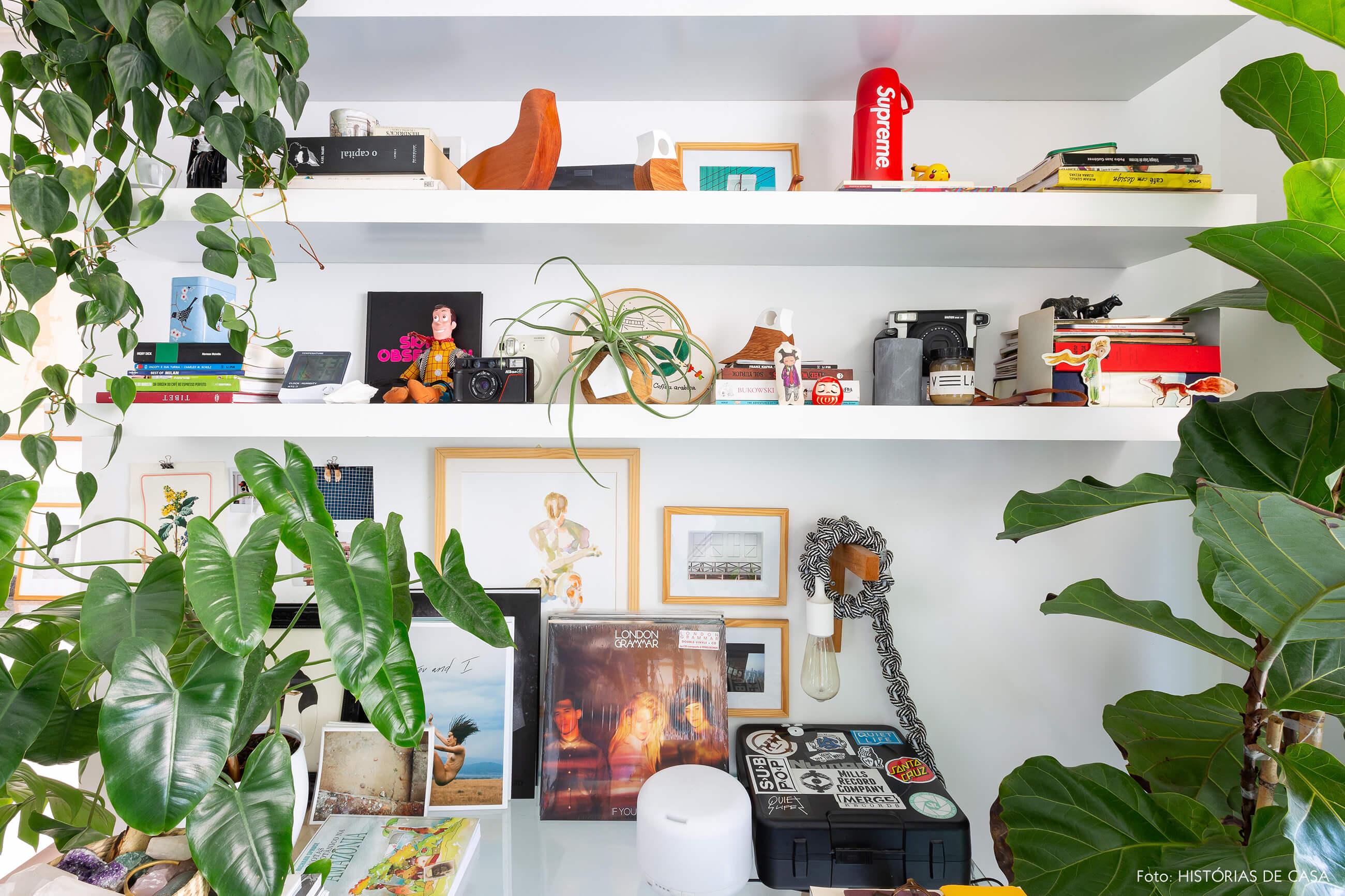 Apartamento pequeno com muitas plantas e home office na sala