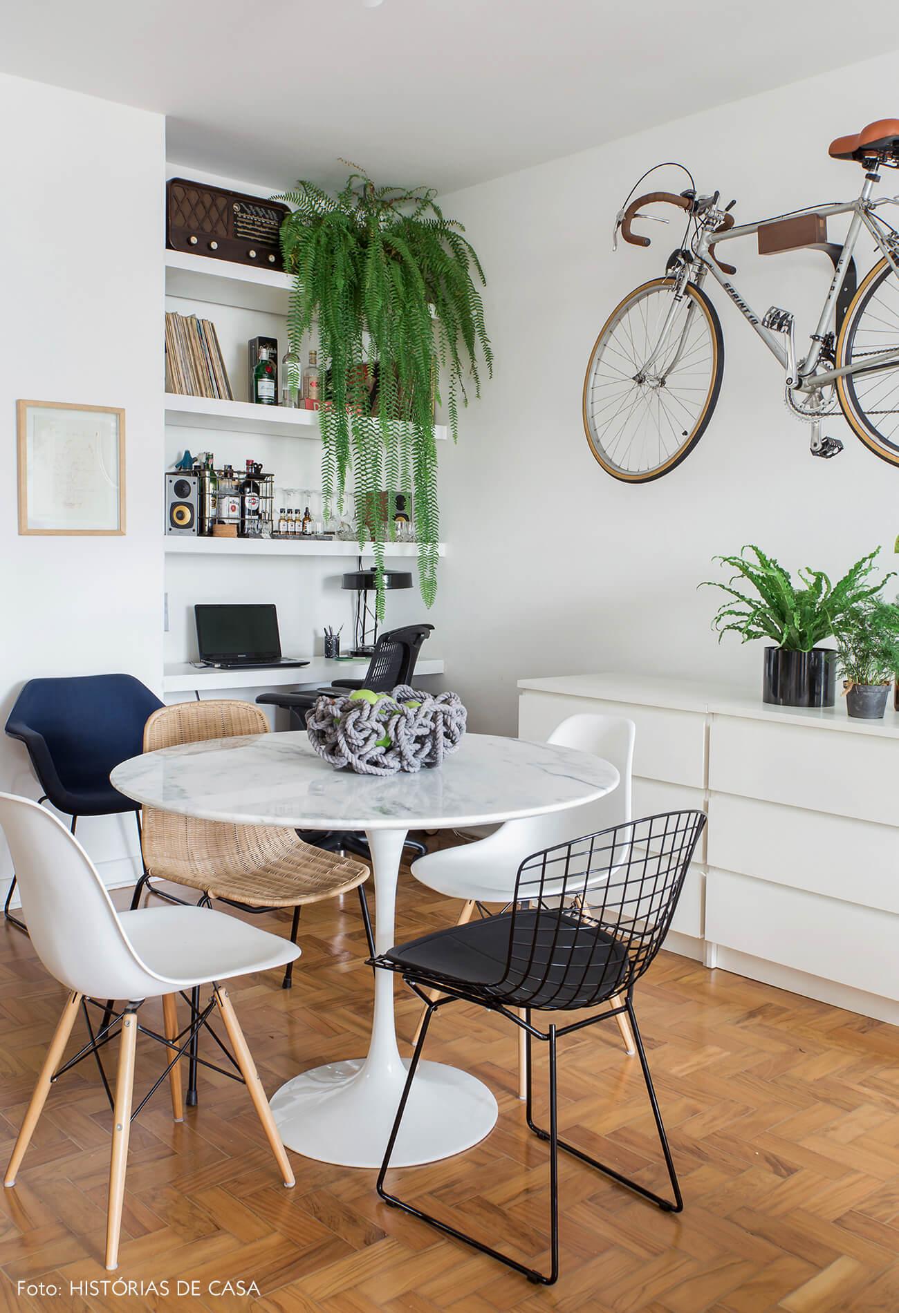 Sala de jantar com mesa tulipa redonda e suporte de bicicleta na parede