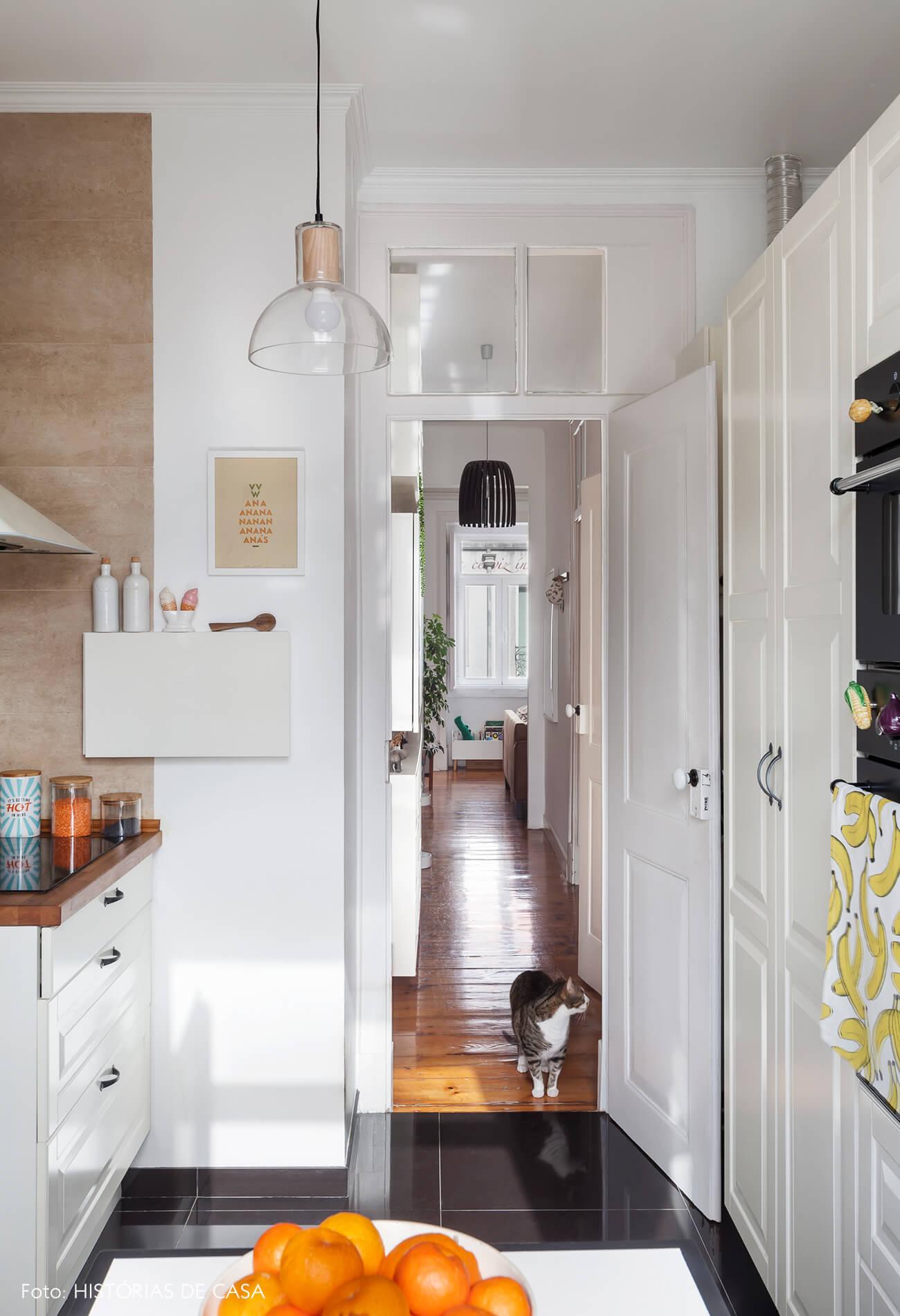 Cozinha com bancada de madeira e piso escuro