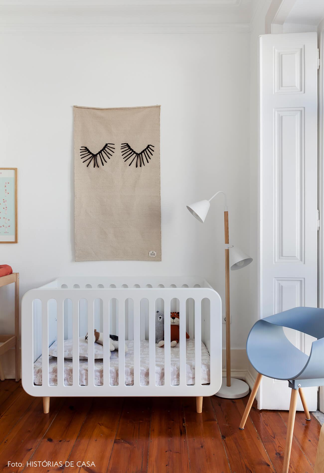 Quarto de bebê com berço branco e tapeçaria