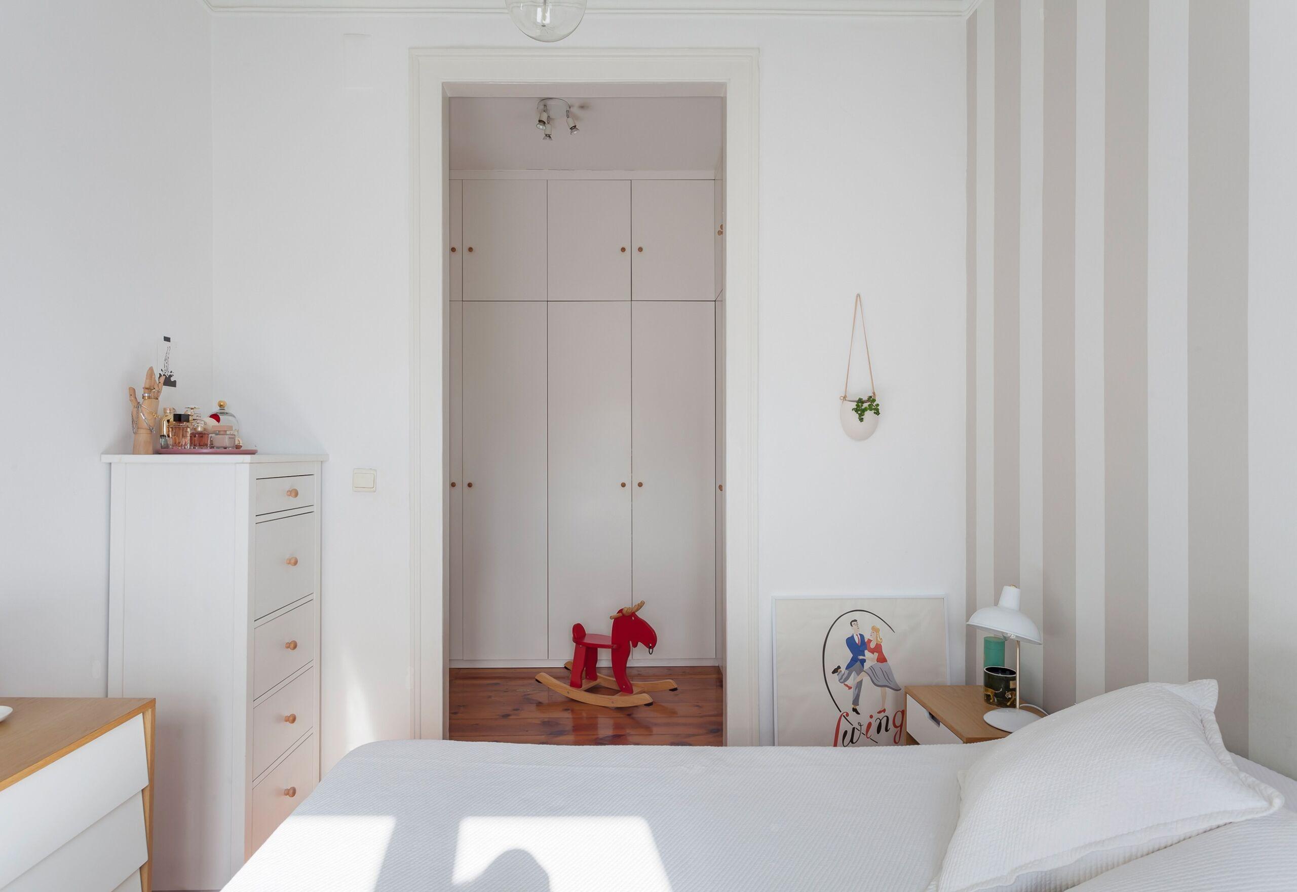 Quarto com papel de parede listrado cinza e closet