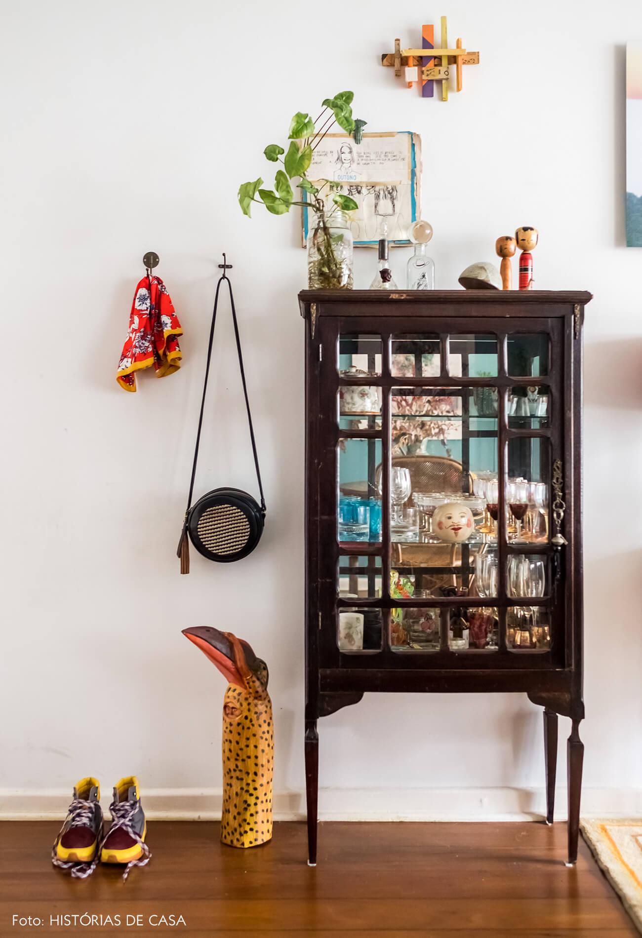 Apartamento com decoração vintage e relíquias garimpadas, como uma cristaleira na entrada da casa