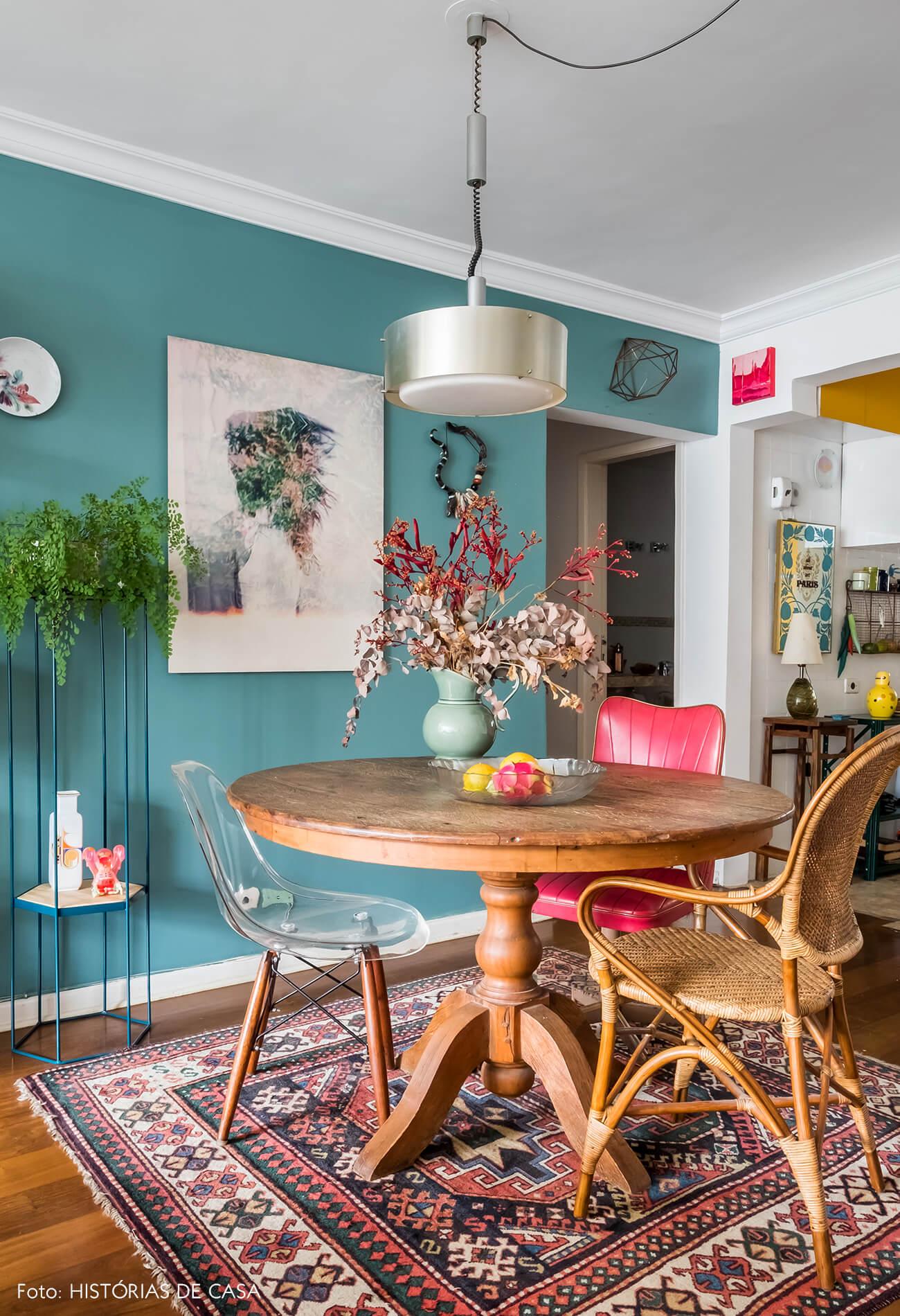 Sala de jantar com mesa redonda e parede pintada de azul