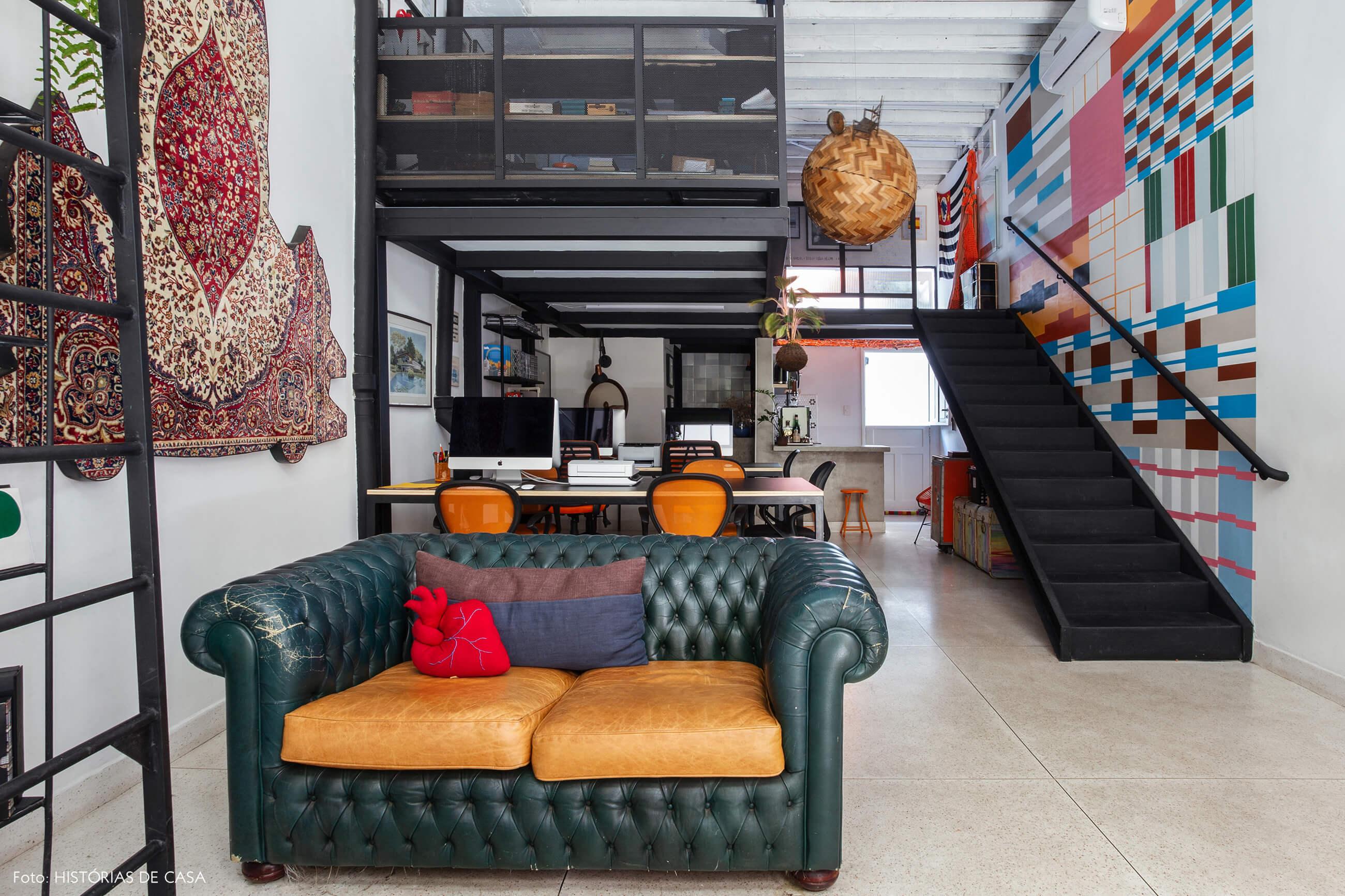 Novo escritório da imobiliária Refúgios Urbanos, sofá vintage de couro e espaço com mezanino