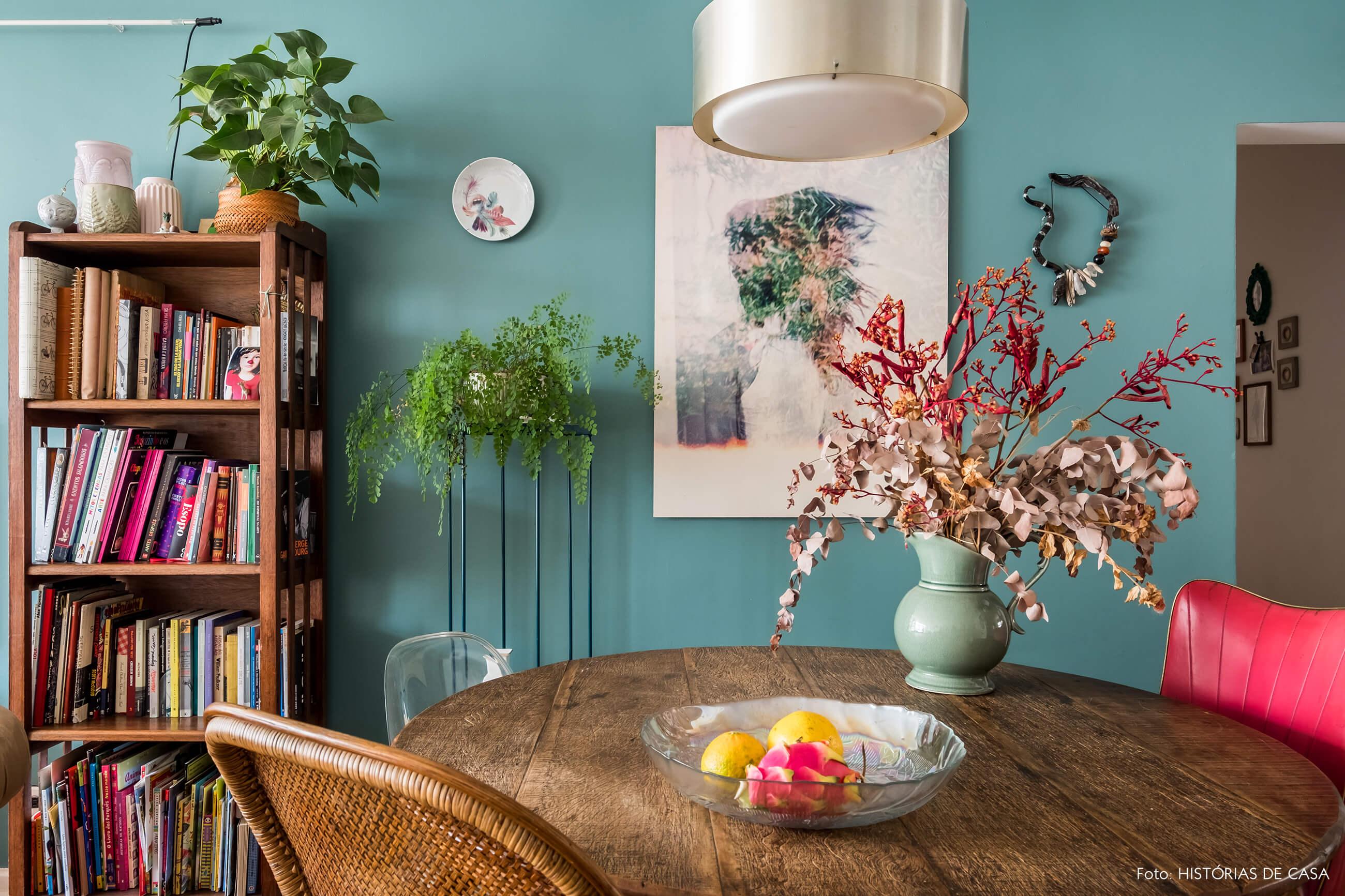 Sala de jantar com mesa redonda e parede pintada de azul, móveis rústicos de madeira