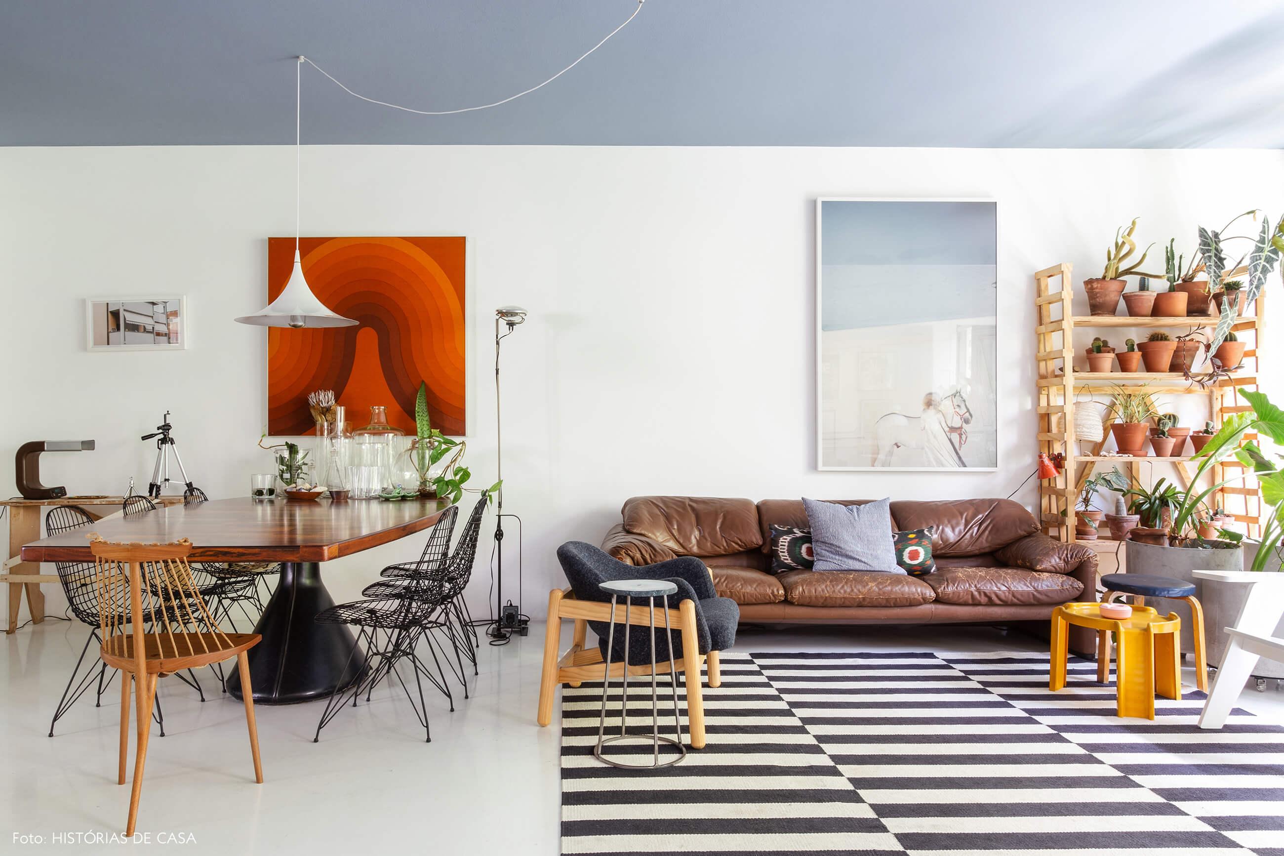 Apartamento do Maurício Arruda, sala integrada com tapete preto e branco e sofá de couro
