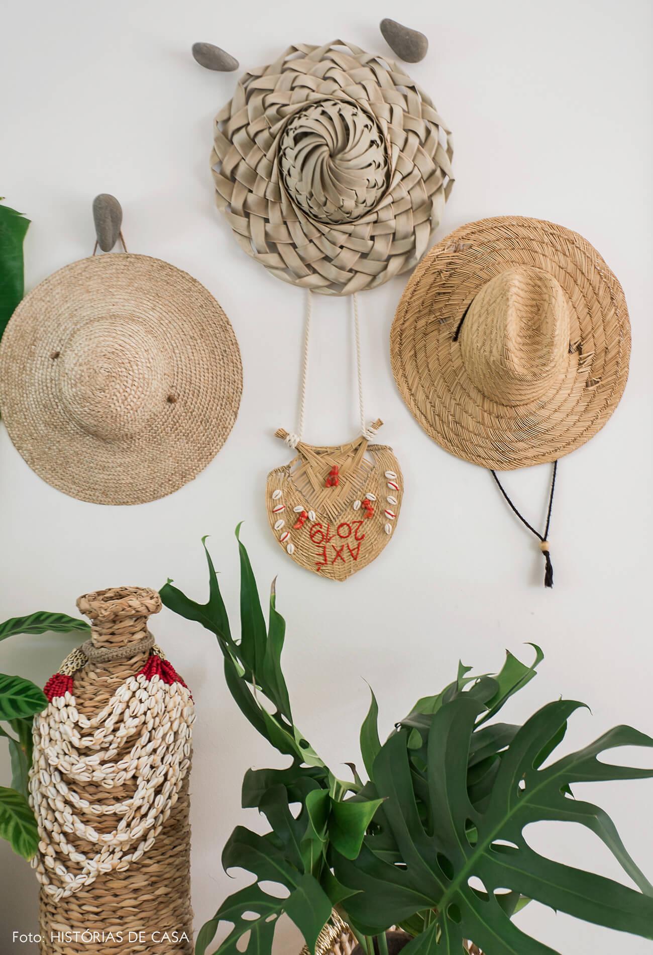 Casa com decoração eclética, cestos e chapéus pendurados na parede