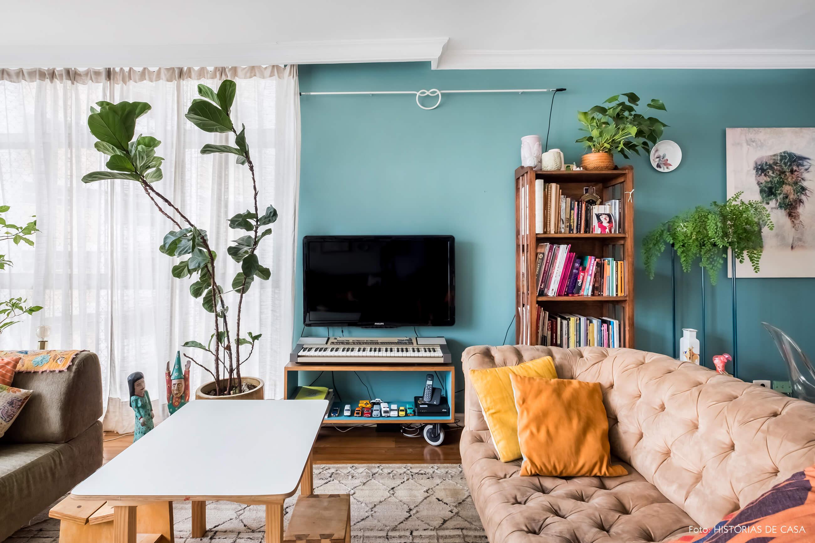 Sala com móveis garimpados e parede pintada de azul esverdeado