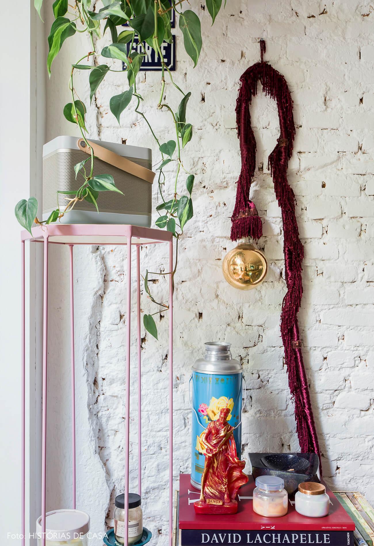 Casa com decoração eclética, parede de tijolinho branco e suporte de plantas