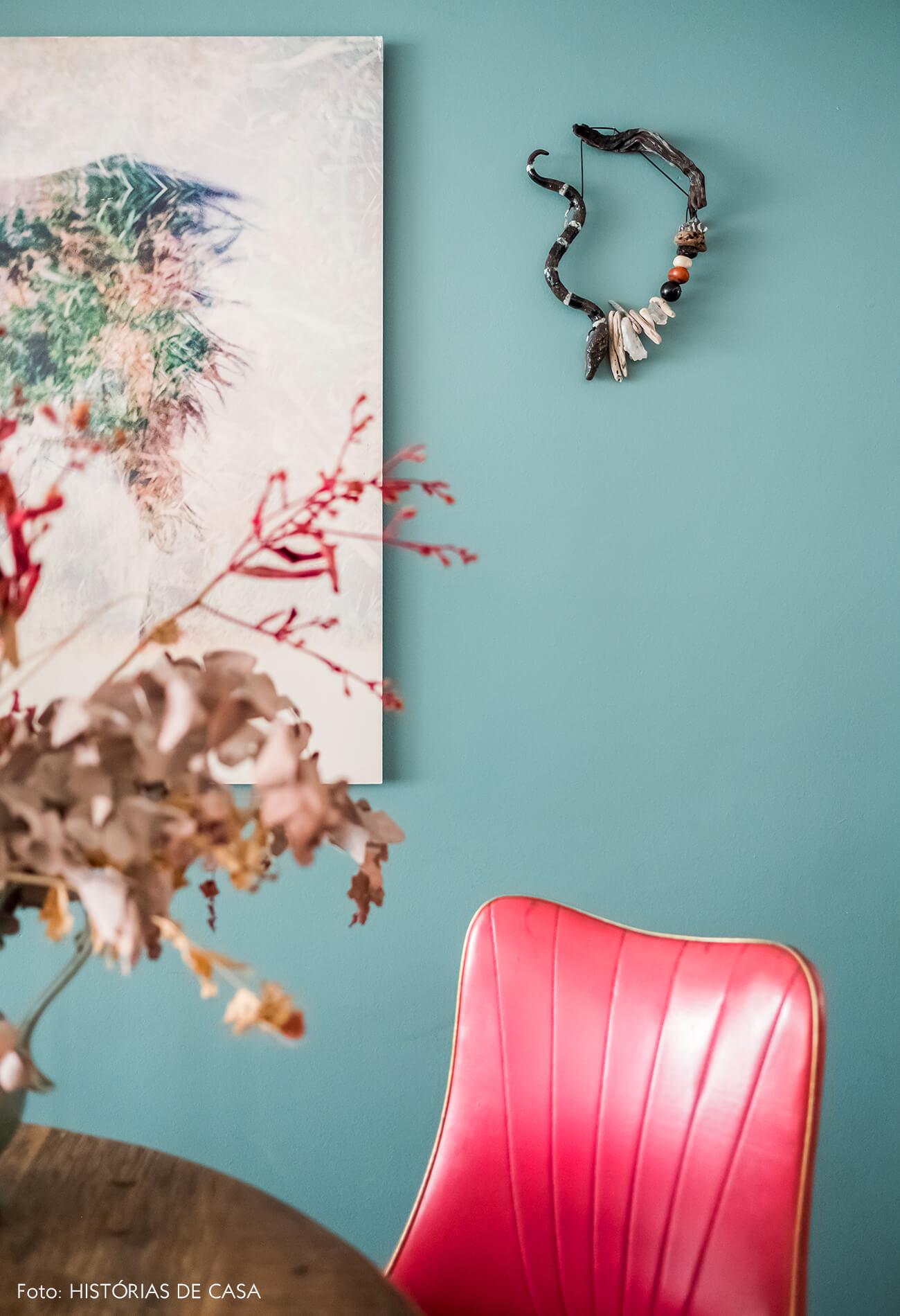 Sala de jantar com mesa redonda e parede pintada de azul, móveis vintage