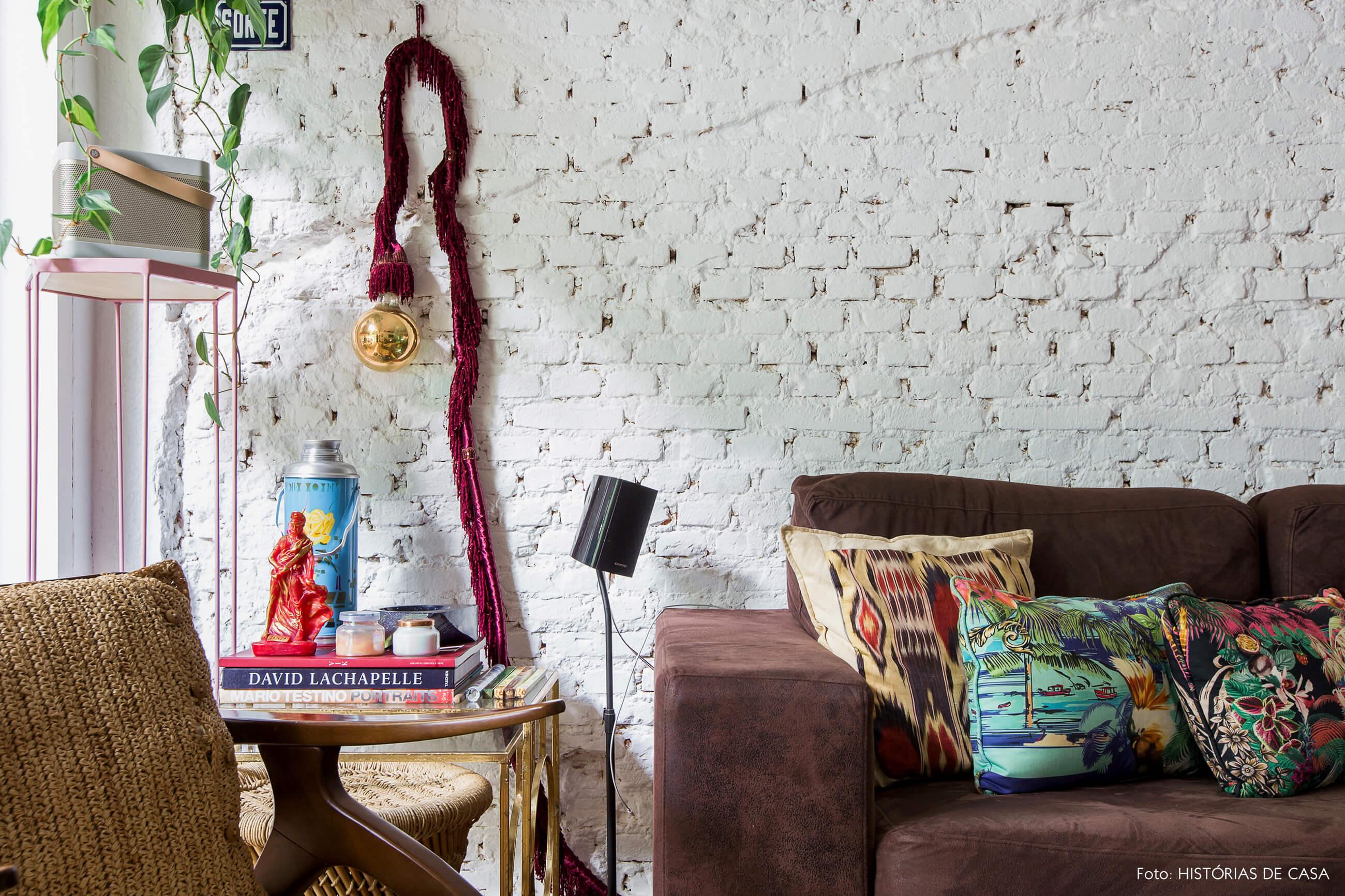 Casa com decoração eclética, parede de tijolinhos brancos e sofá escuro