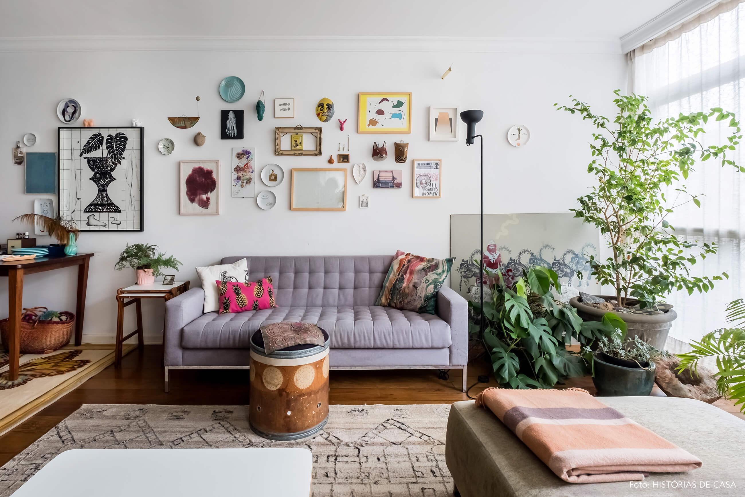 Apartamento integrado, sala com sofá cinza e plantas