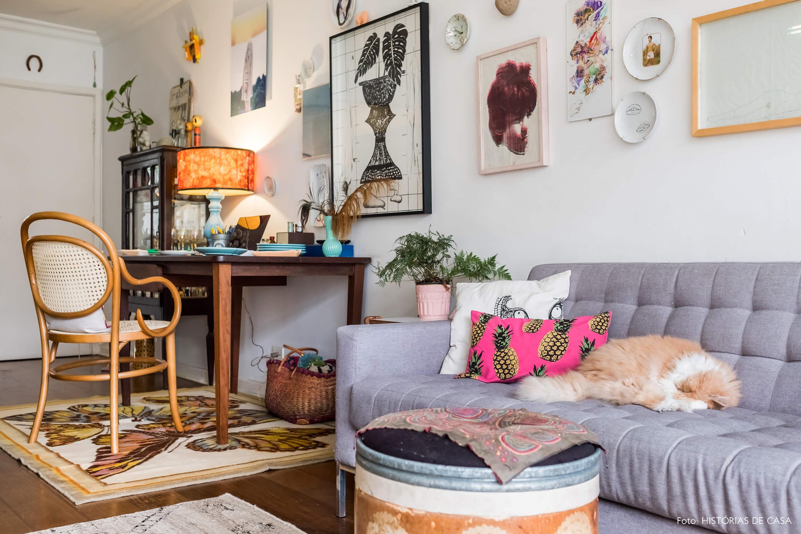 Sala com sofá cinza, quadrinhos e home office