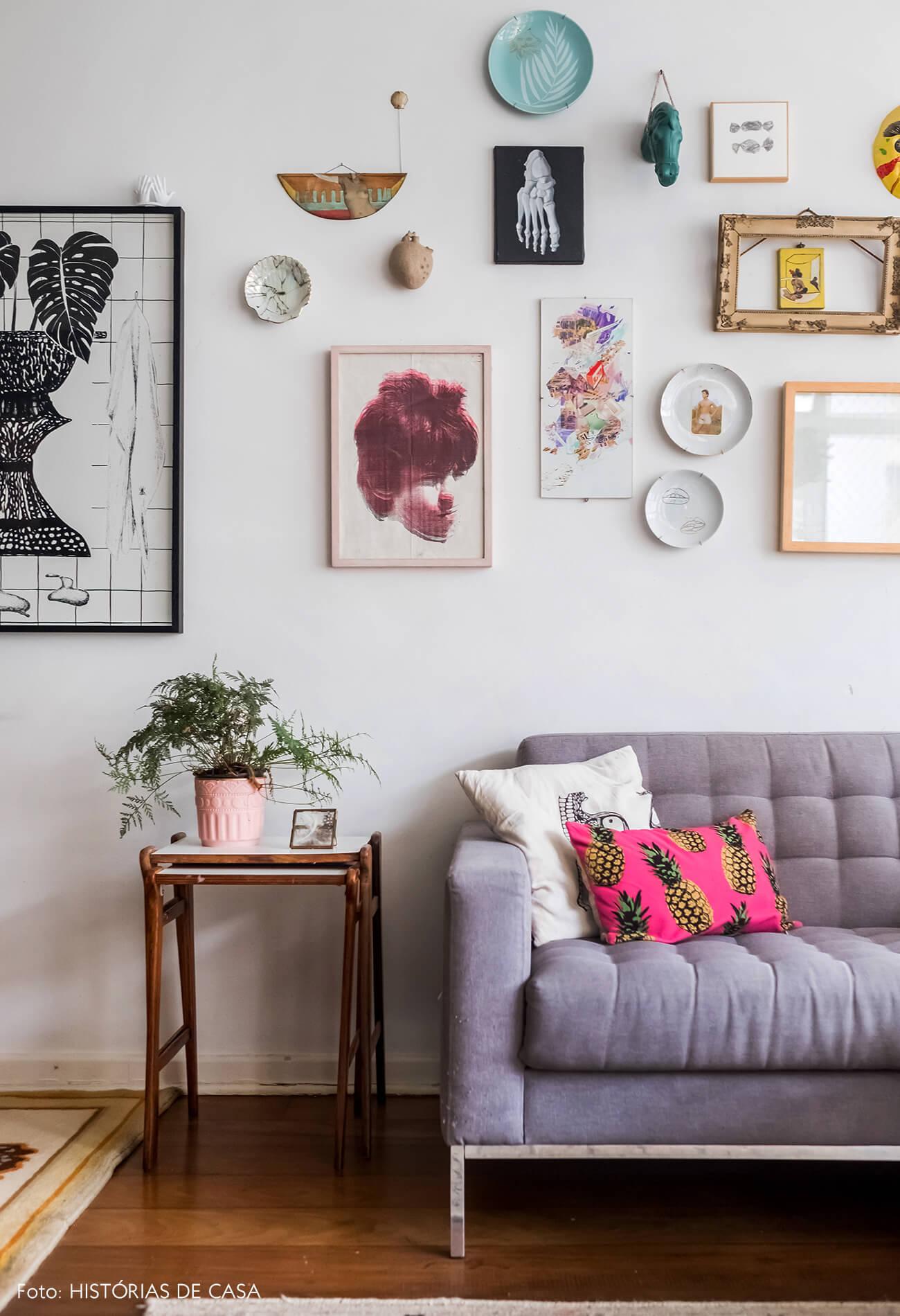Sala com sofá cinza e parede de quadrinhos