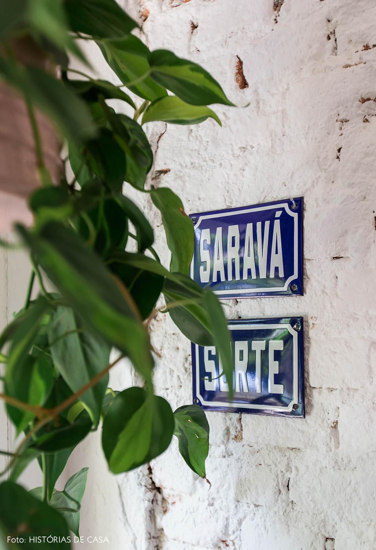Casa com decoração eclética, parede de tijolinhos brancos e placa de Saravá