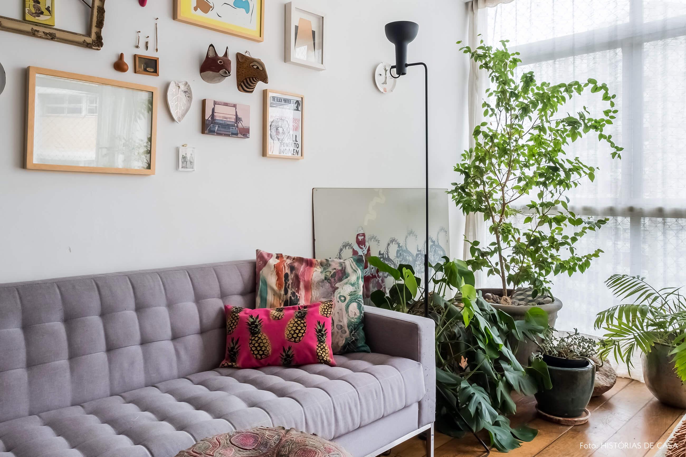 Sala com sofá cinza e muitas plantas