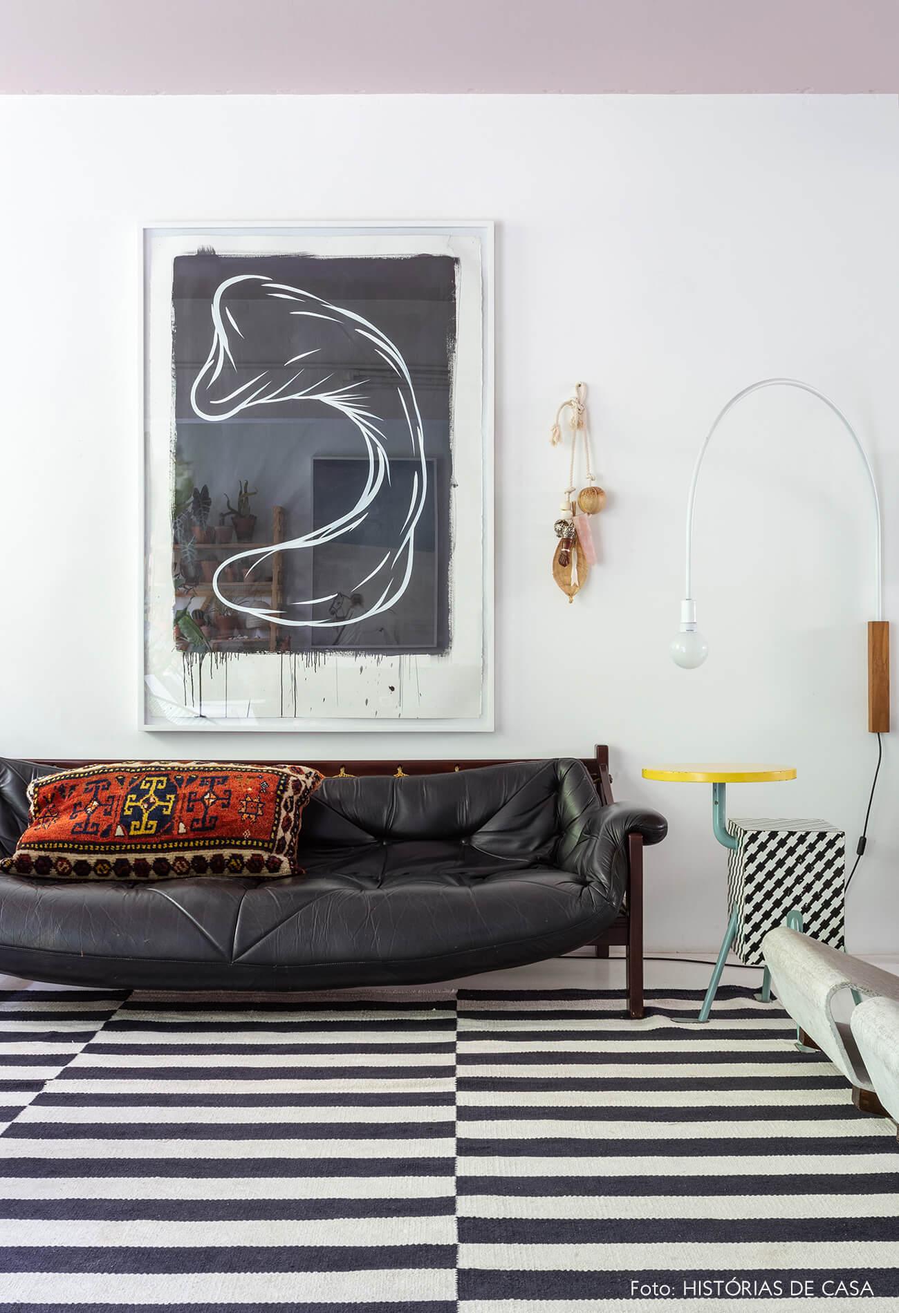 Apartamento do Maurício Arruda, sala com tapete preto e branco e sofá de couro