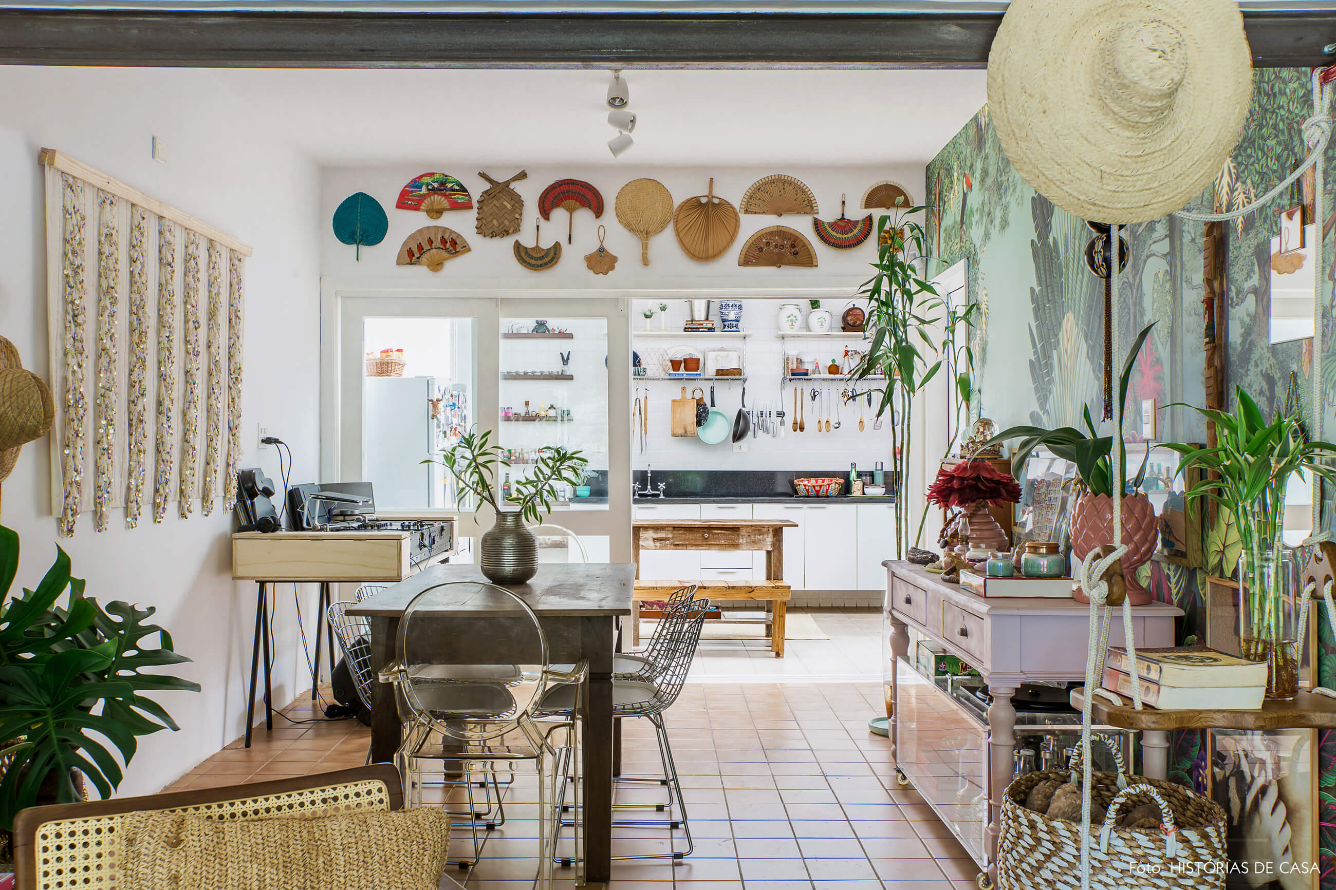 Casa com decoração eclética, sala de jantar com portas de correr de vidro para a cozinha