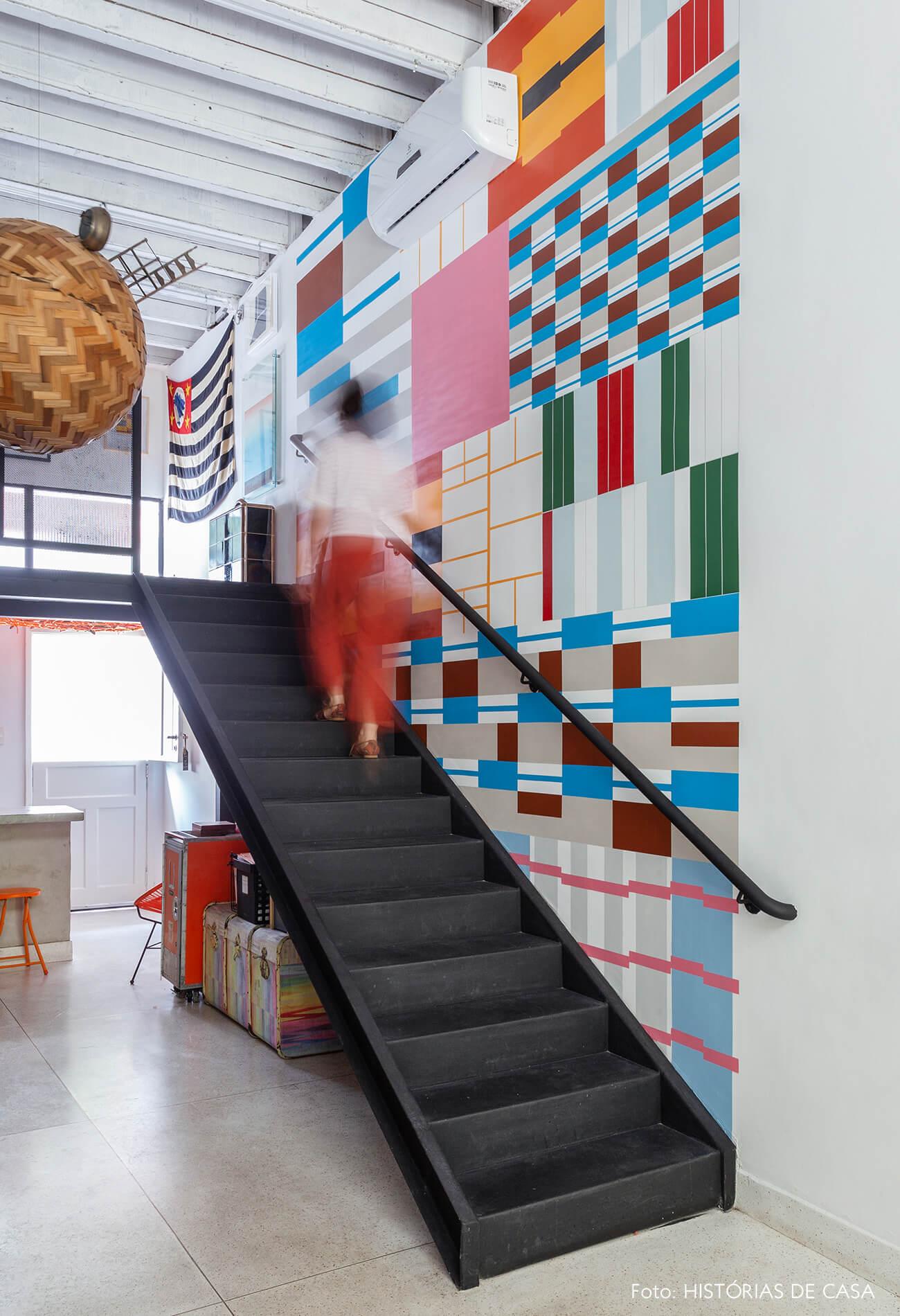 Escada de serralheria preta e adesivo colorido na parede