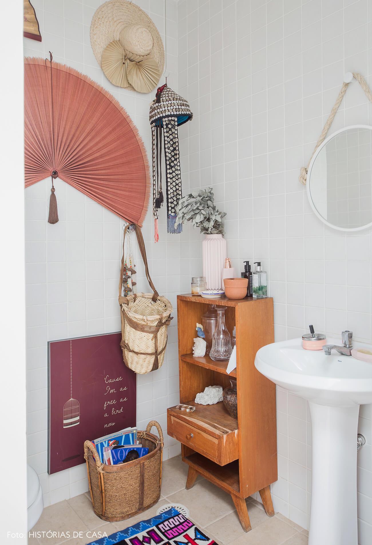 Casa com decoração eclética, lavabo com leques de parede pendurados