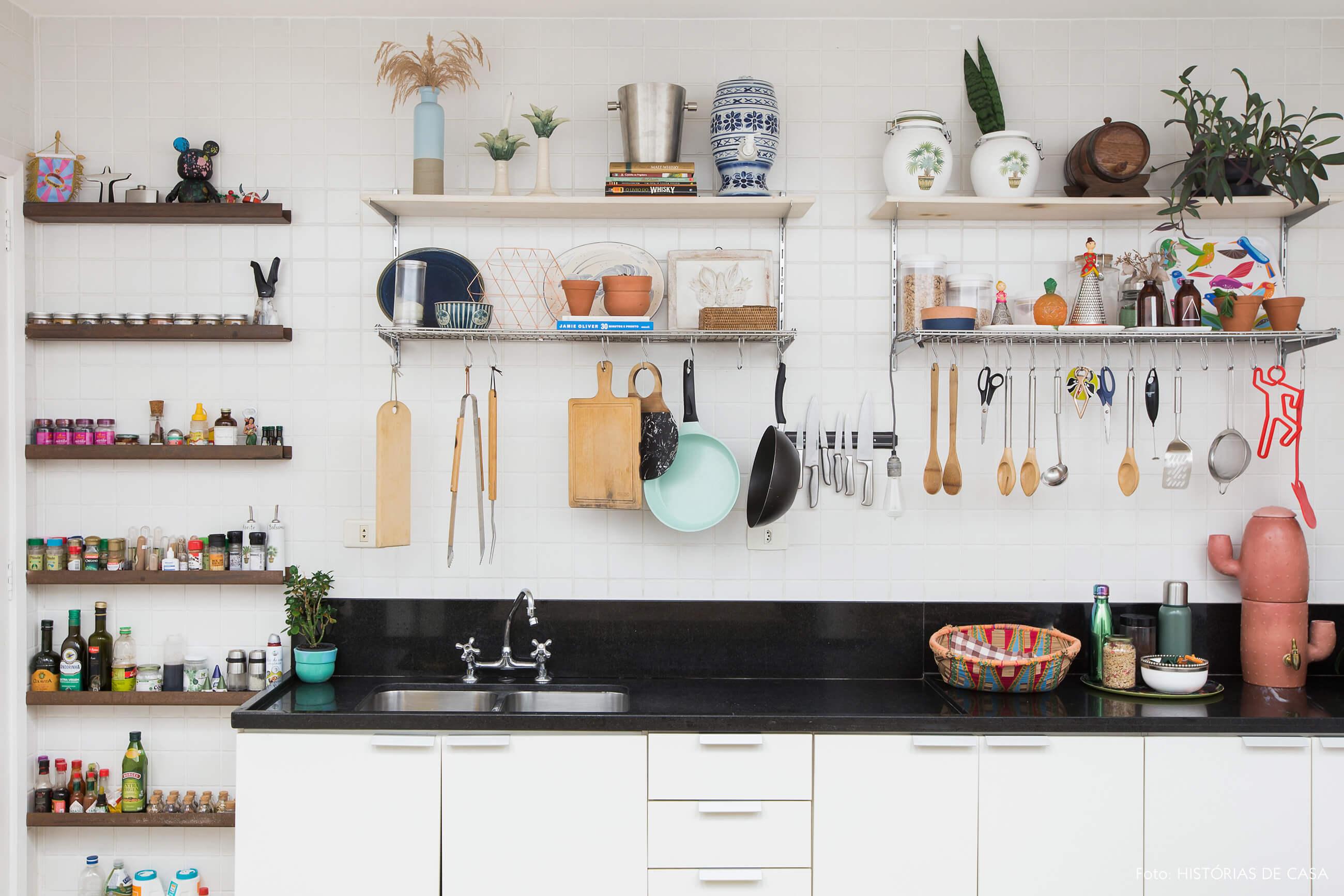 Cozinha com azulejos simples e prateleiras aramadas sobre a pia