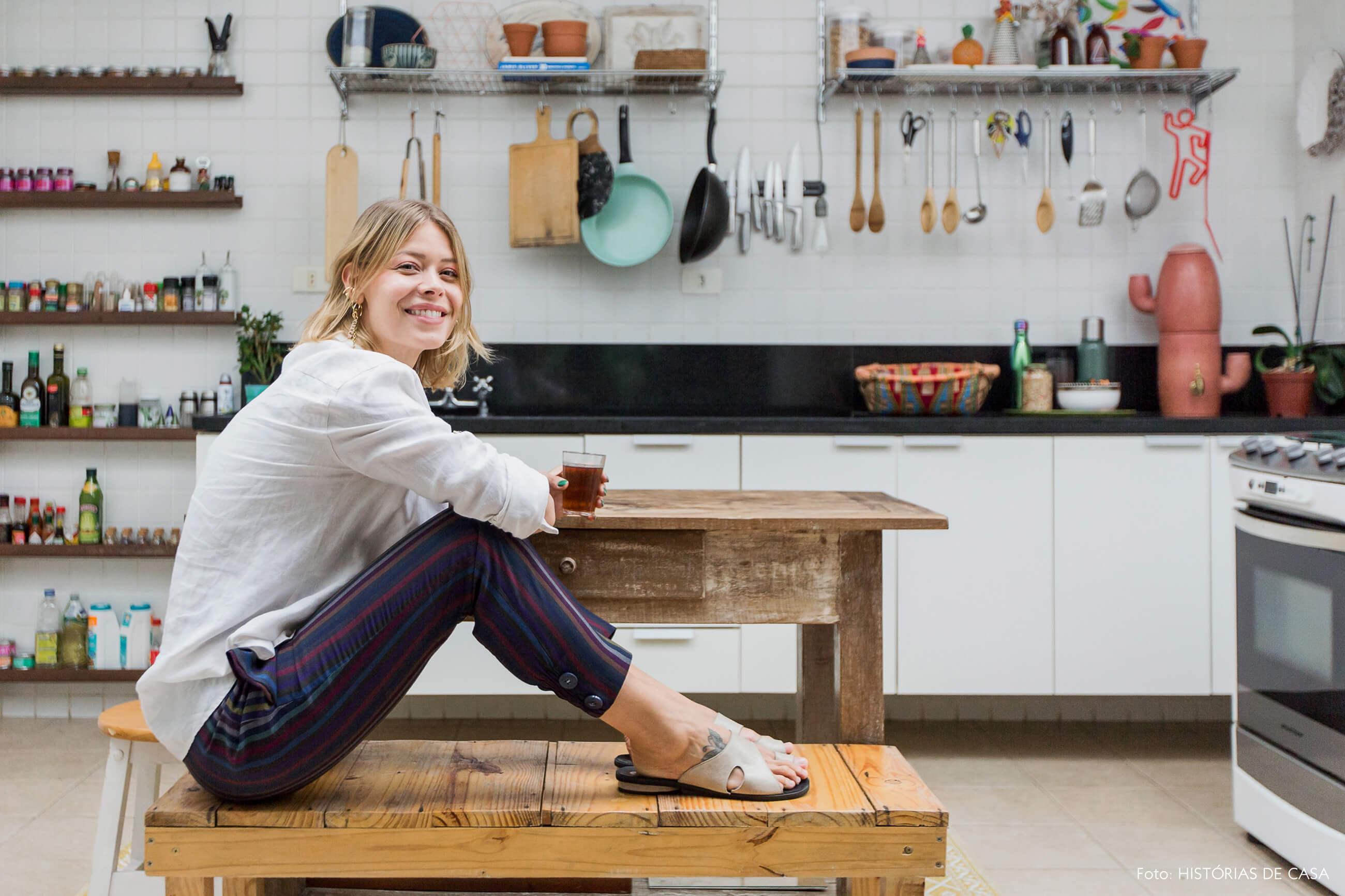 Cozinha com móveis simples, mesa e banco de madeira de demolição