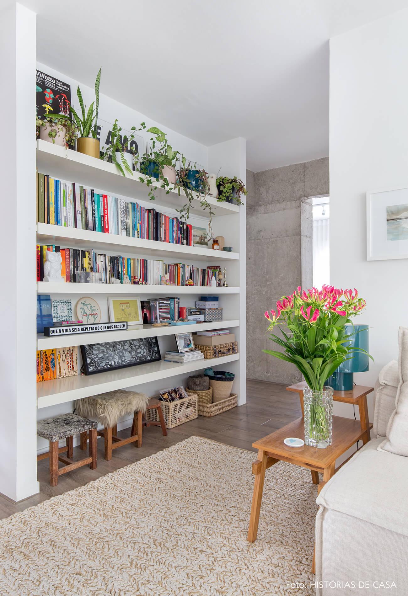 Estante embutida em recuo no corredor, livros coloridos e plantas