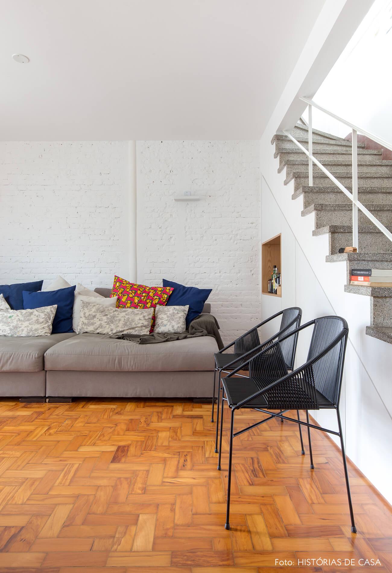 Sala com sofá cinza e parede de tijolinho branco