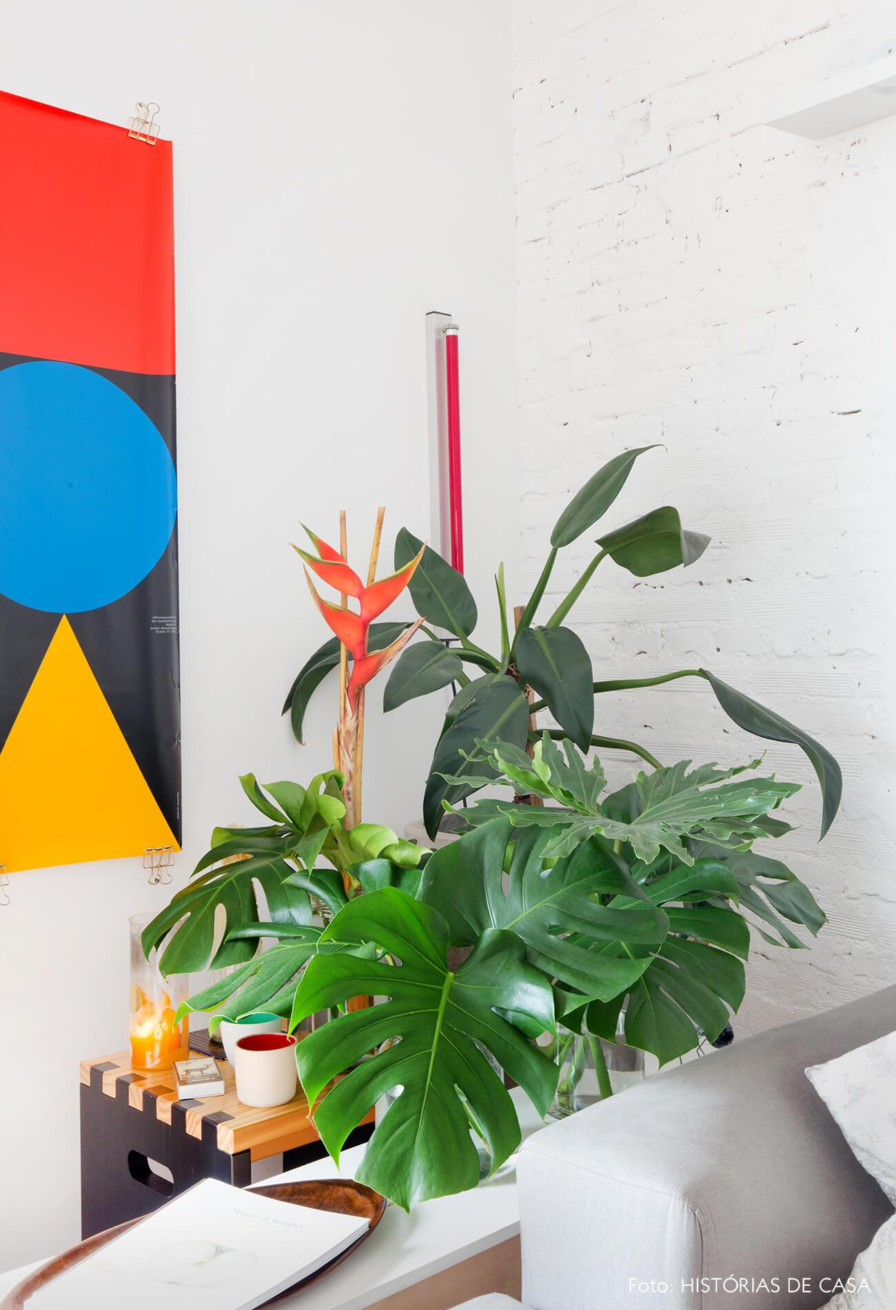 Sala com parede de tijolinho branco e muitas plantas na lateral do sofá