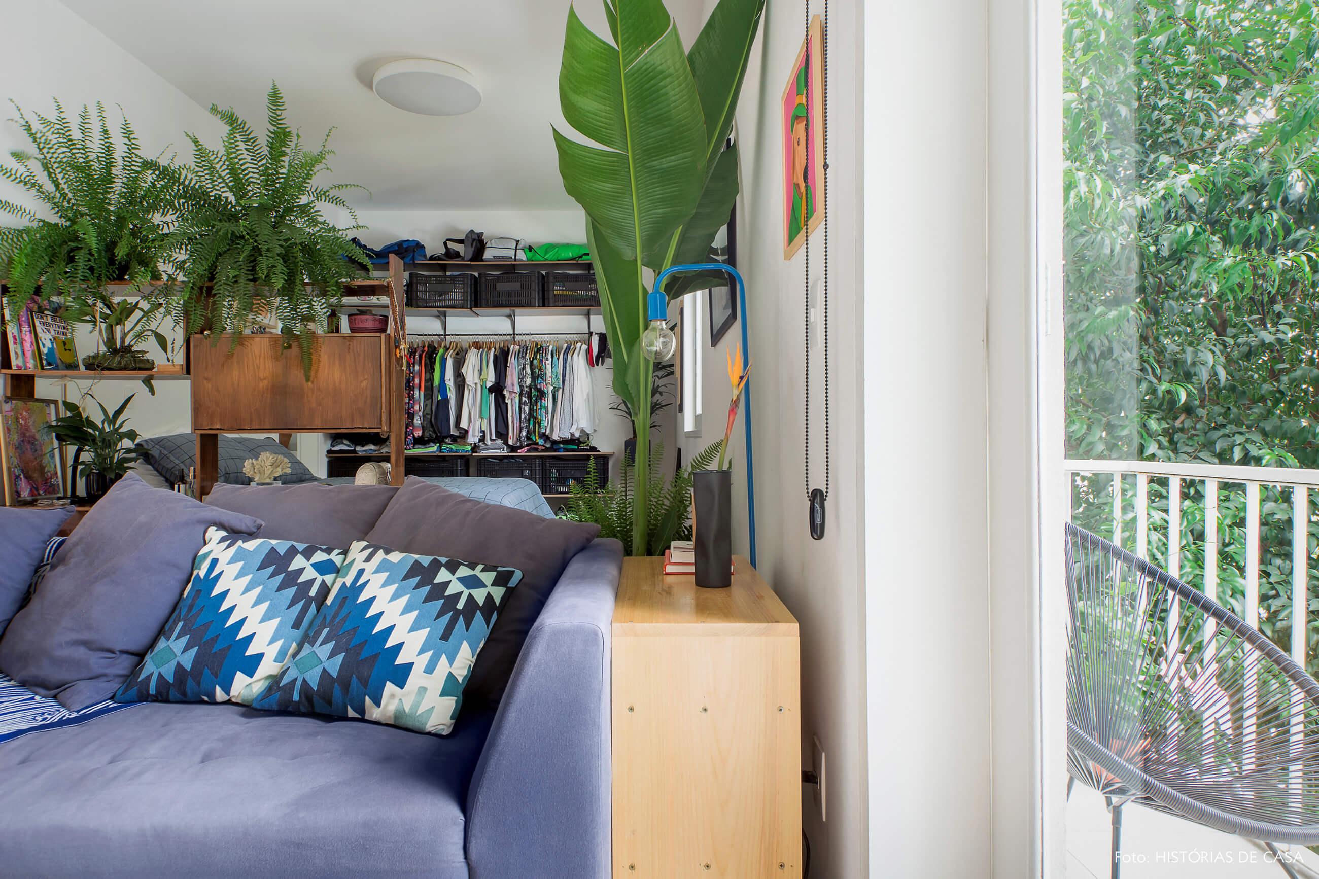 Sala integrada ao quarto com pequena varanda e muitas plantas