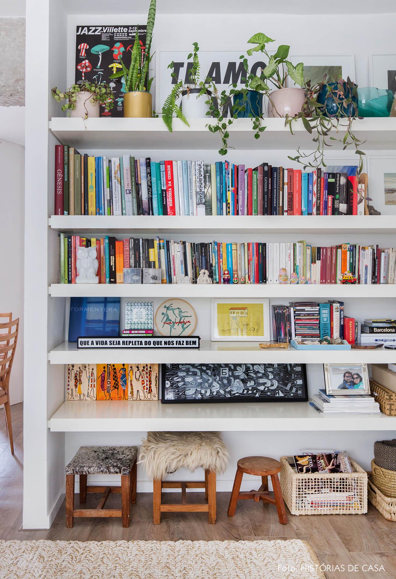 Estante branca do piso ao teto com livros coloridos