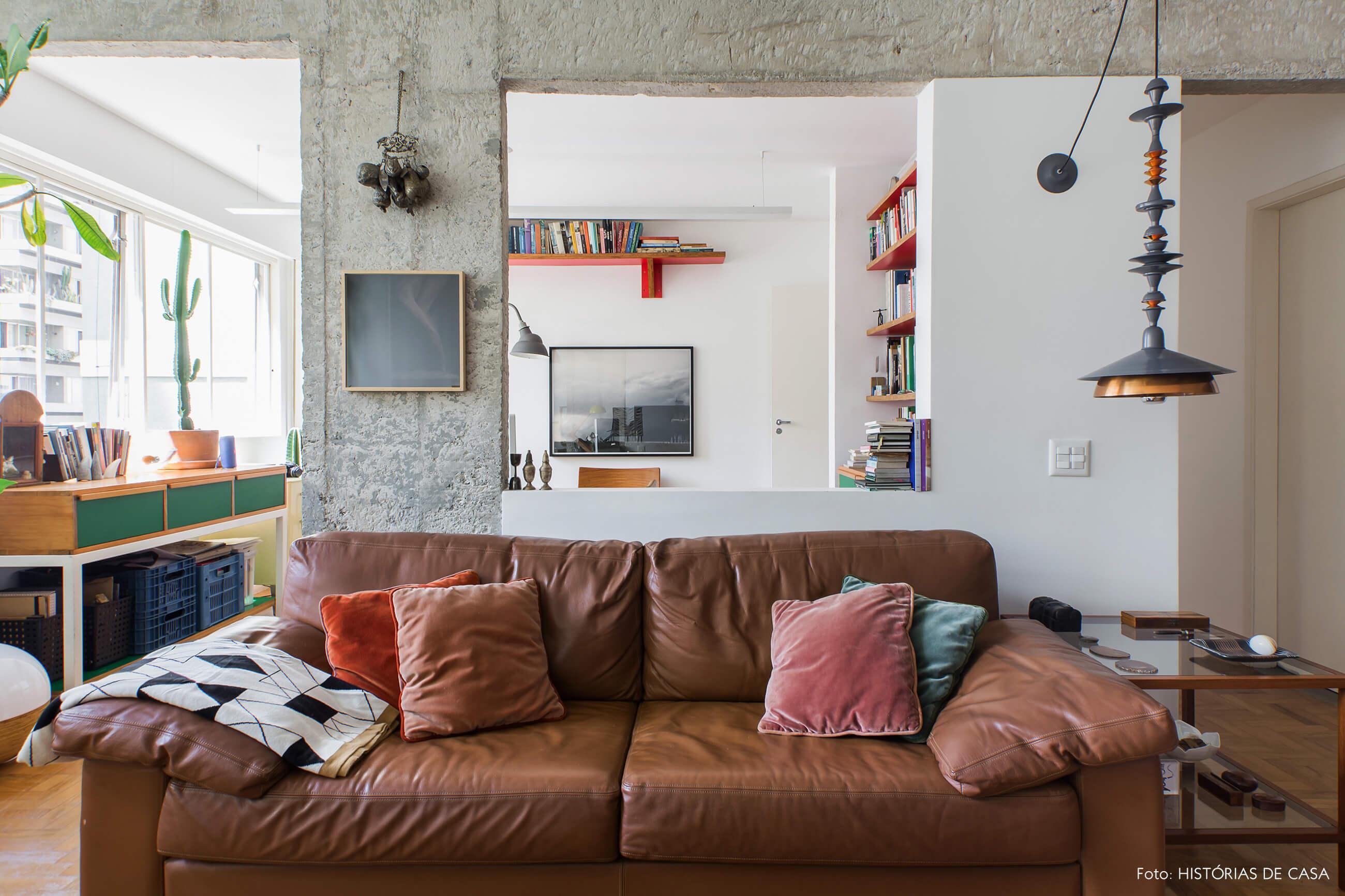 Sala com sofá de couro marrom e janela integrada para home office