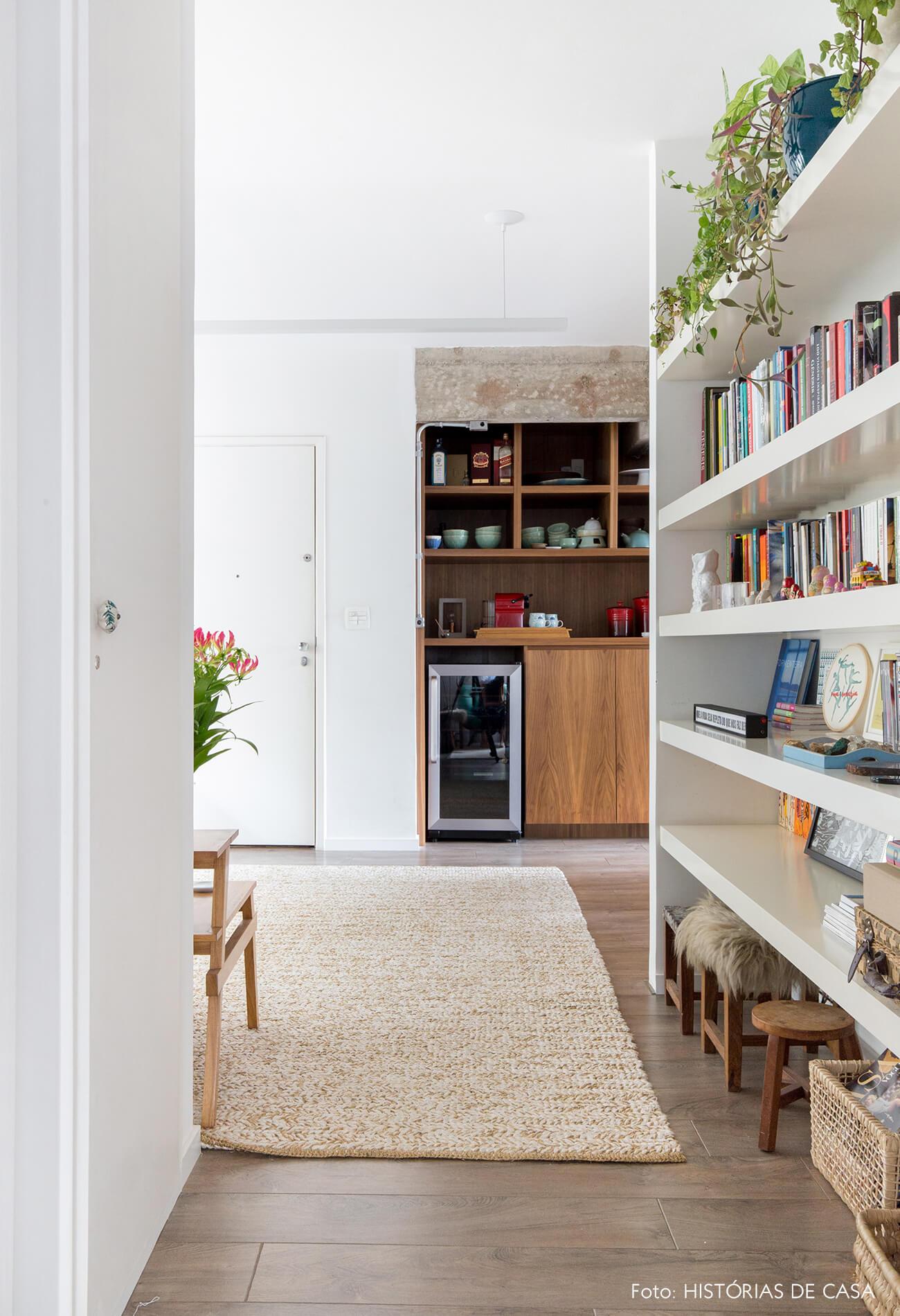 Apartamento com estante no corredor que leva aos quartos