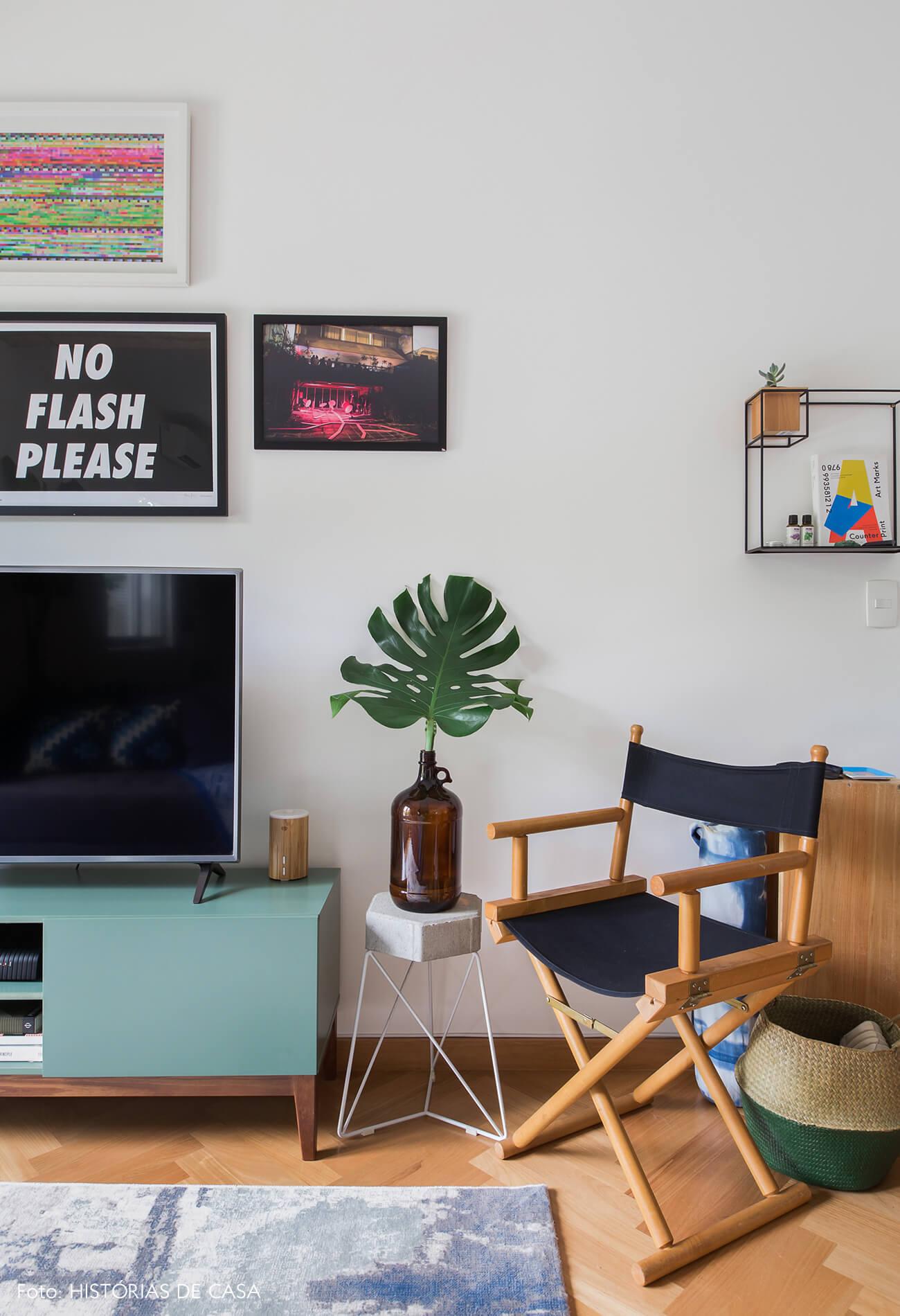 Apartamento alugado com decoração inspiradora, parede de quadros atrás da televisão e cadeira diretor