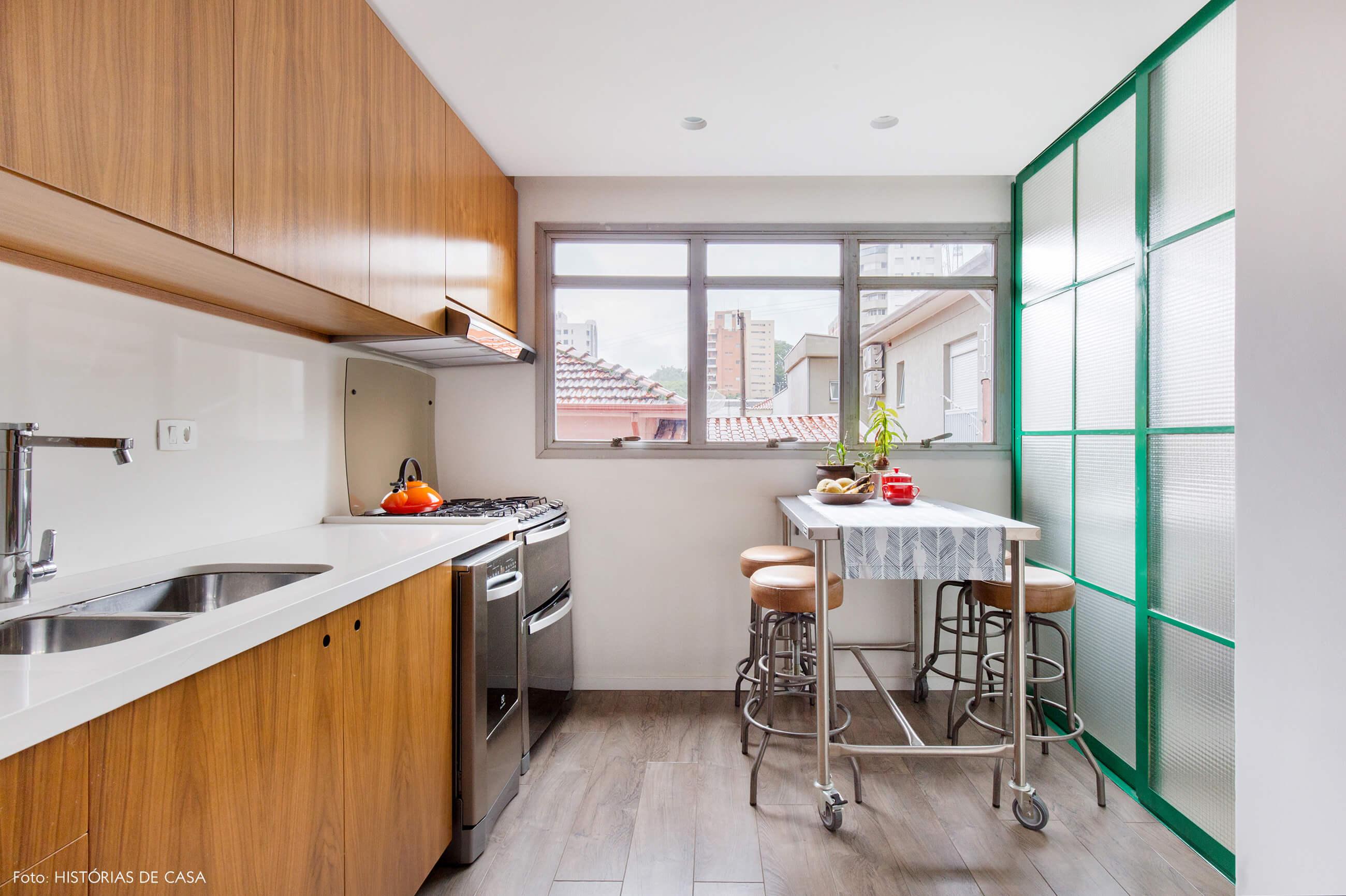Cozinha reformada com bancada industrial com rodinhas e porta de serralheria verde
