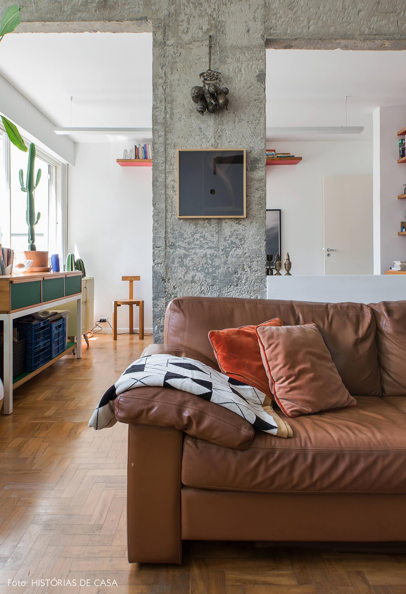 Sala integrada com pilar de concreto e sofá marrom de couro