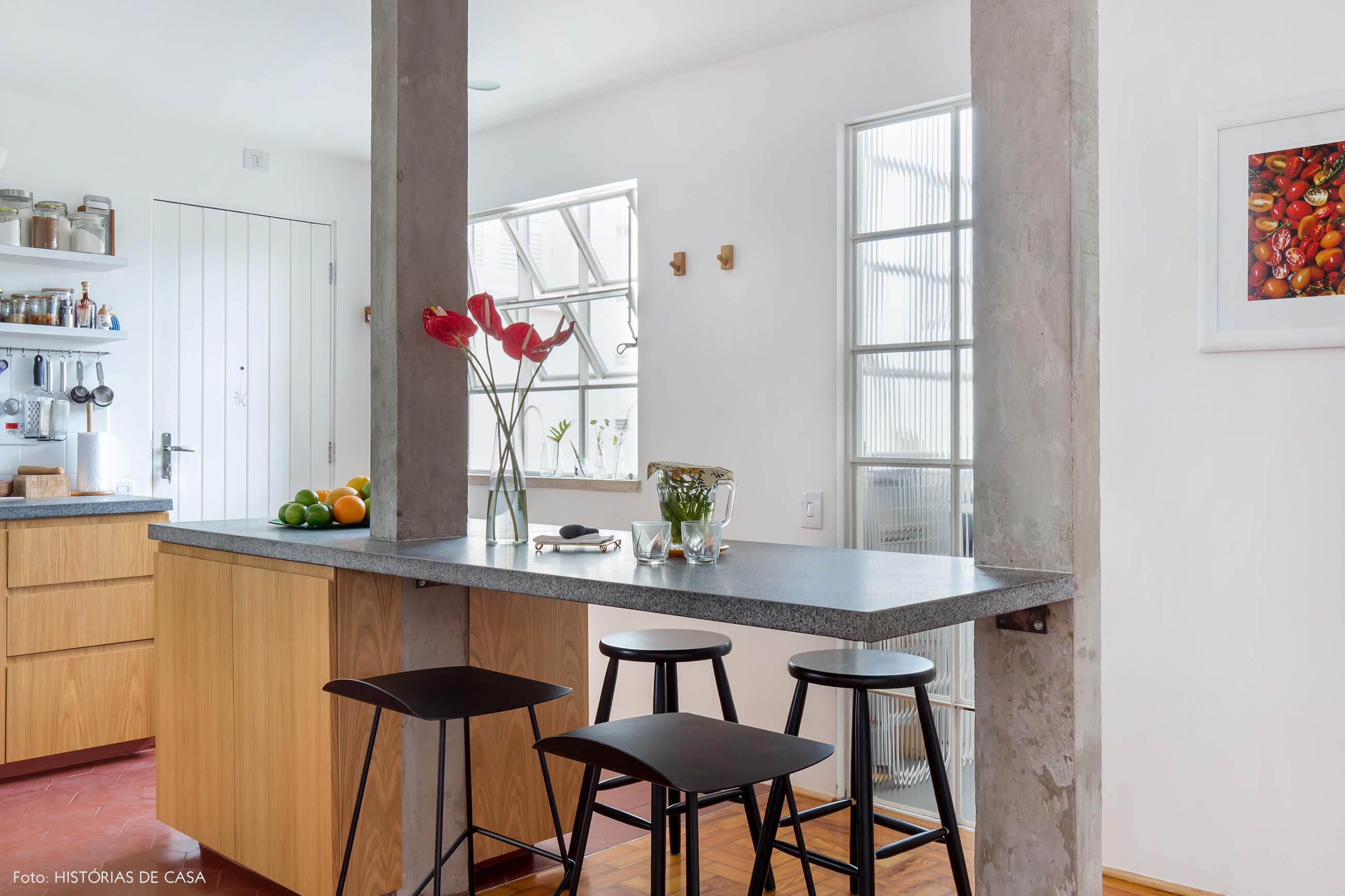 Cozinha reformada com ilha central e bancada de marcenaria