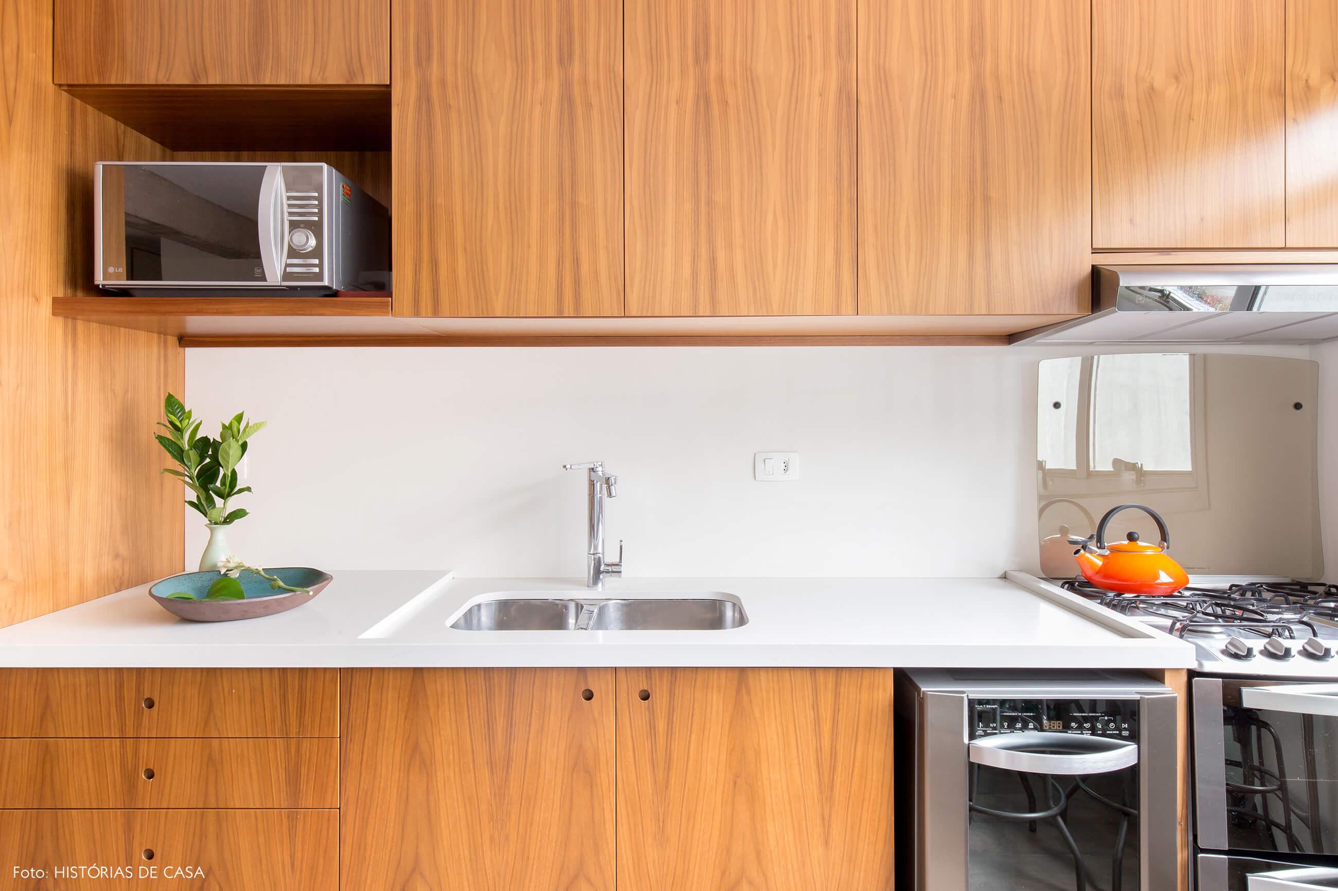 Cozinha reformada com bancada branca e armários de madeira