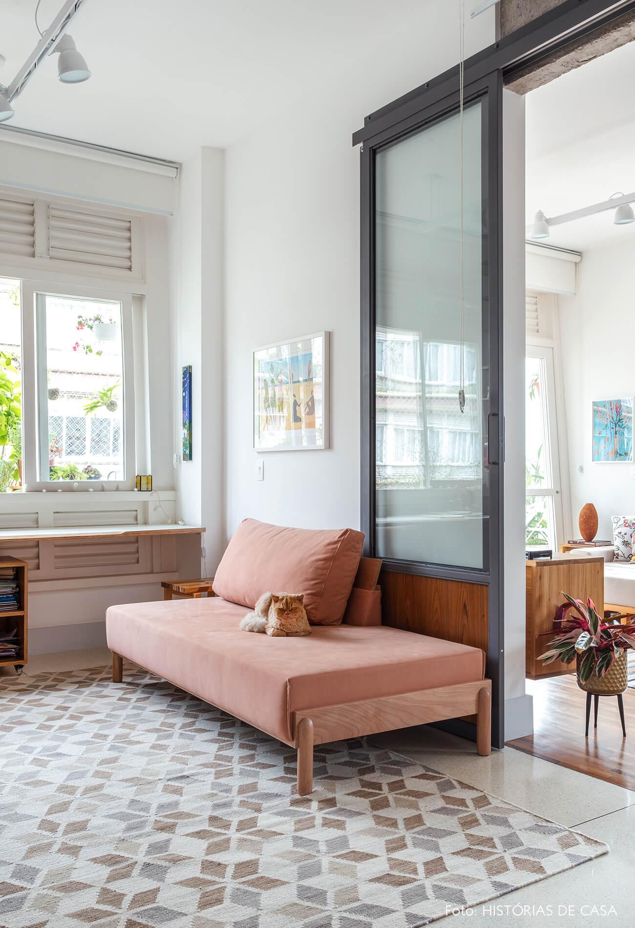 Home office com sofá rosa e porta de serralheria e vidro
