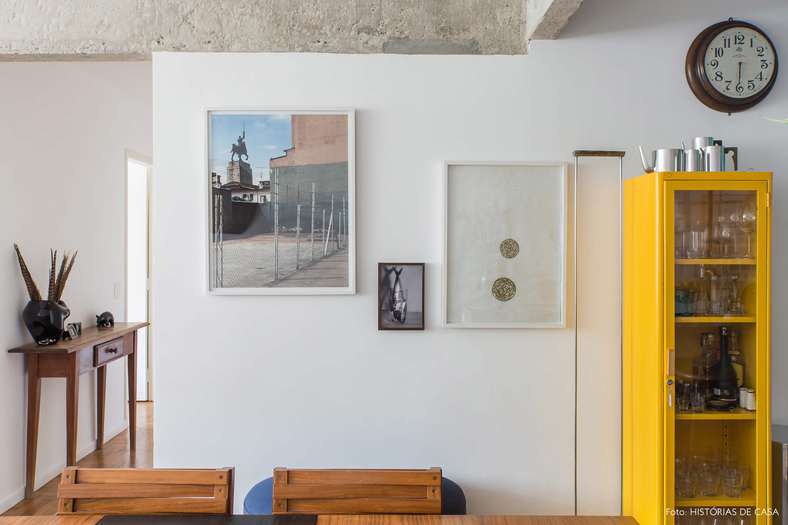 Parede de quadros e armário antigo amarelo