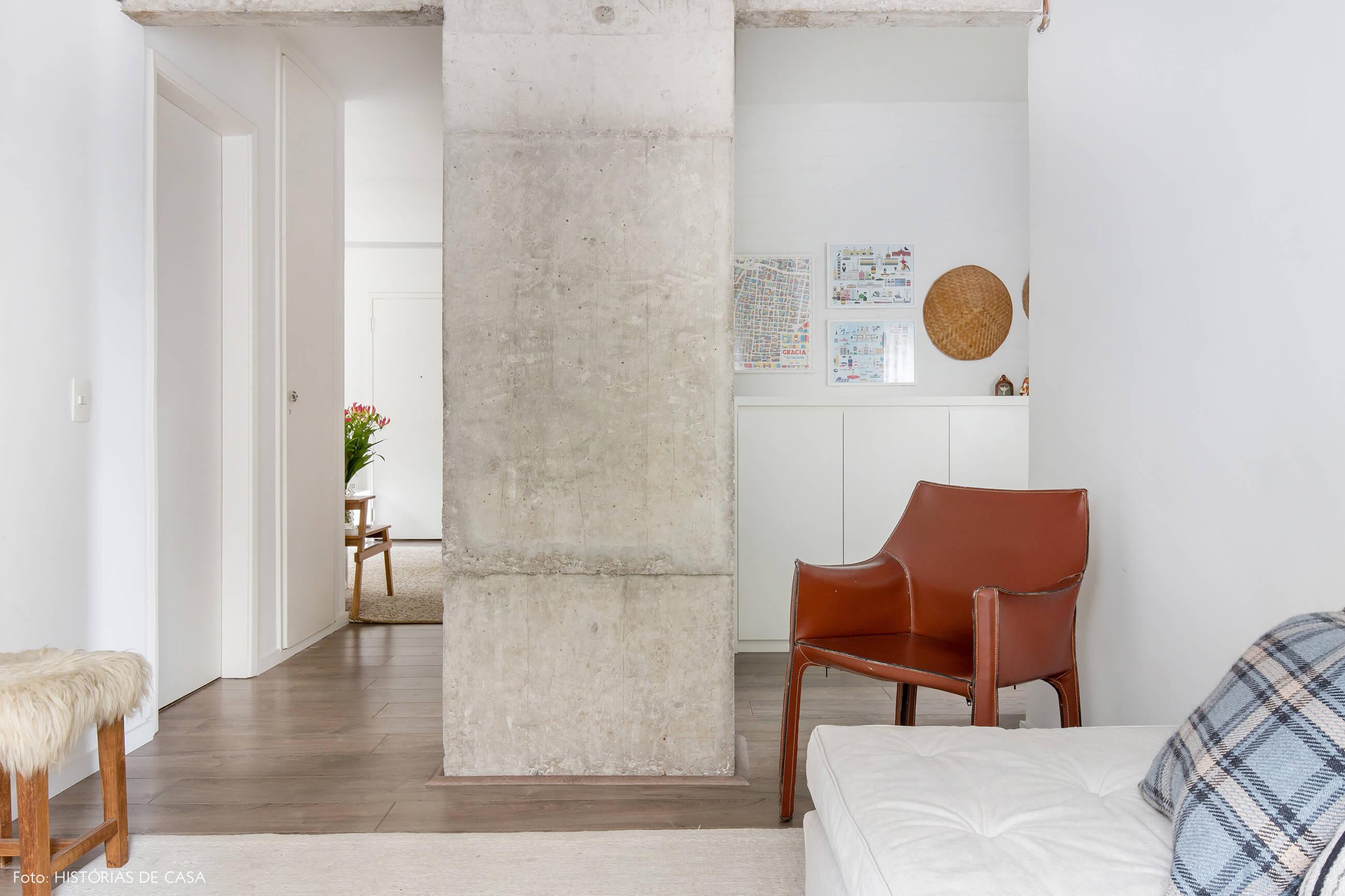 Sala aconchegante com pilar de concreto e poltrona de couro