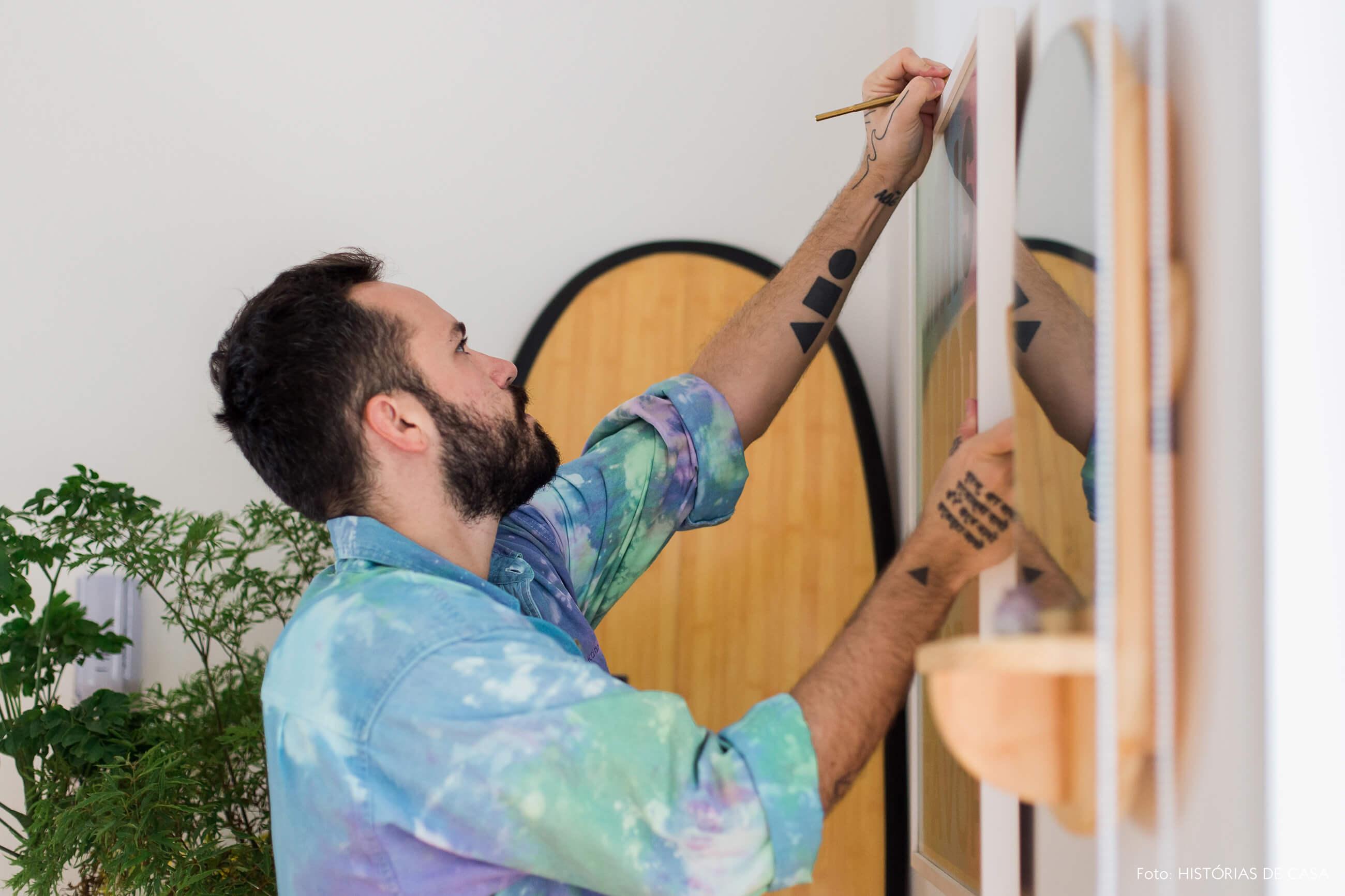 Felipe pendurando quadros na parede