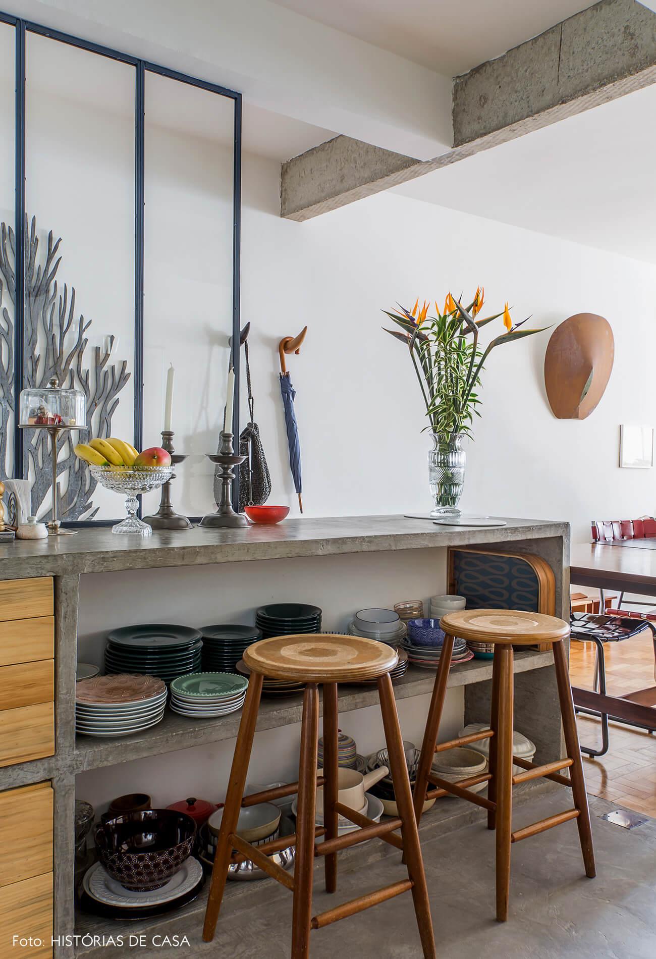 Cozinha com bancada de concreto e louças à mostra