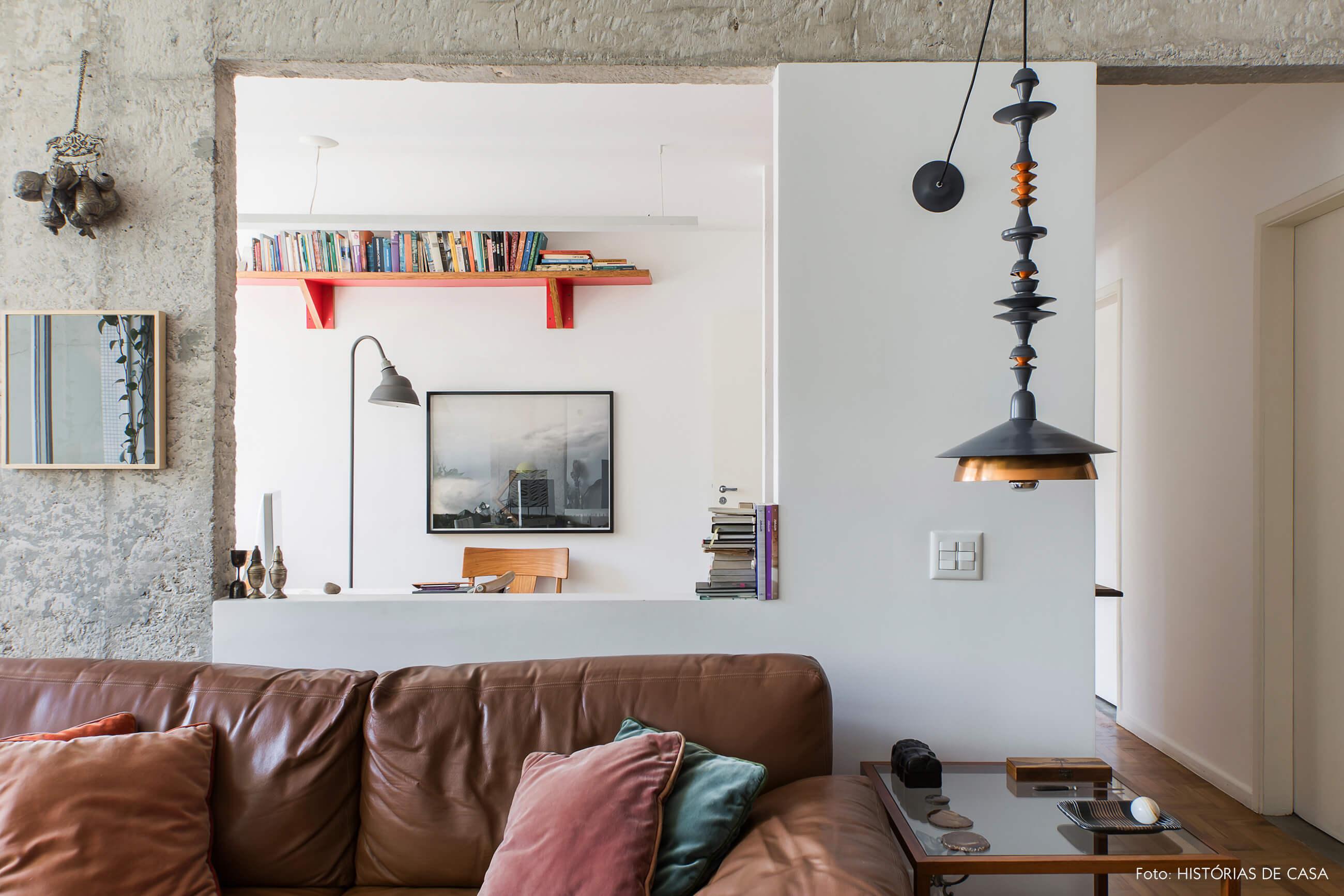 Sofá de couro marrom e abertura na parede com pilares de concreto