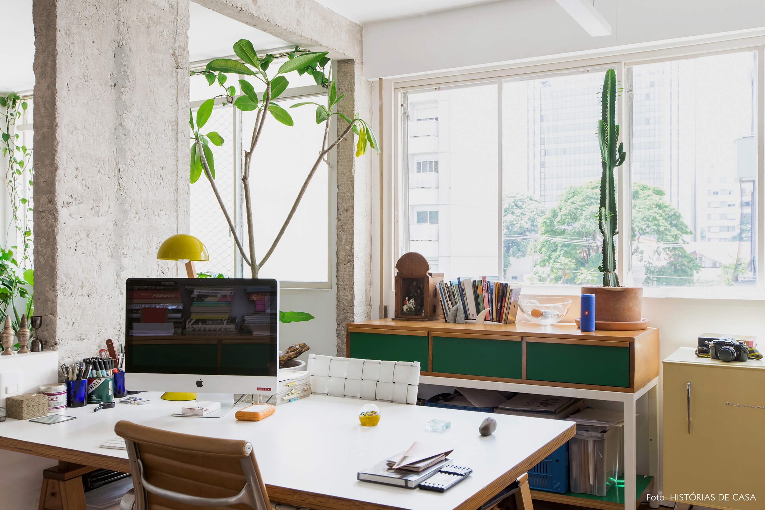 Home office com móvel de formica colorida e muitas plantas