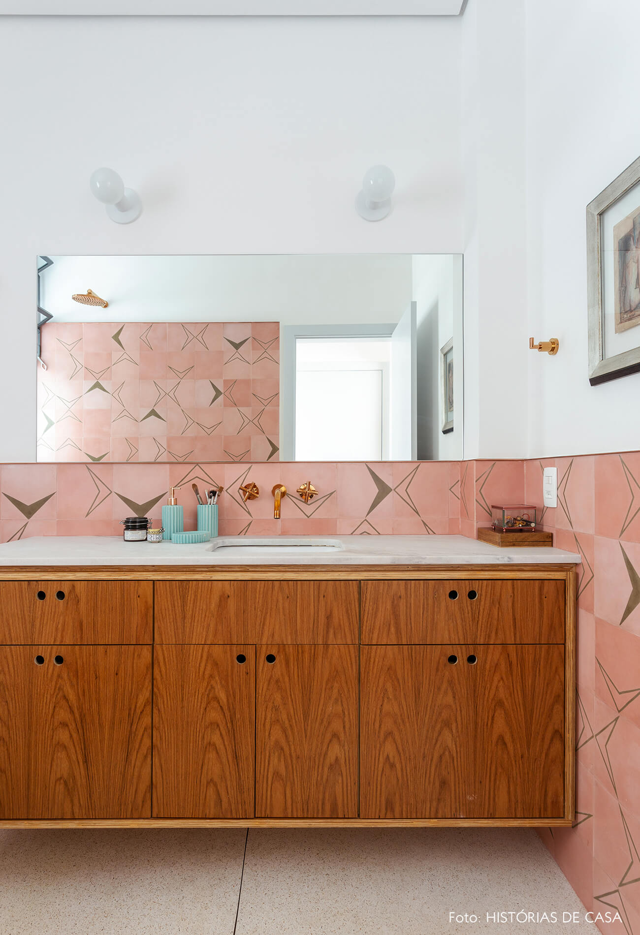 Banheiro com parede de ladrilhos hidráulicos rosa e marcenaria sob medida