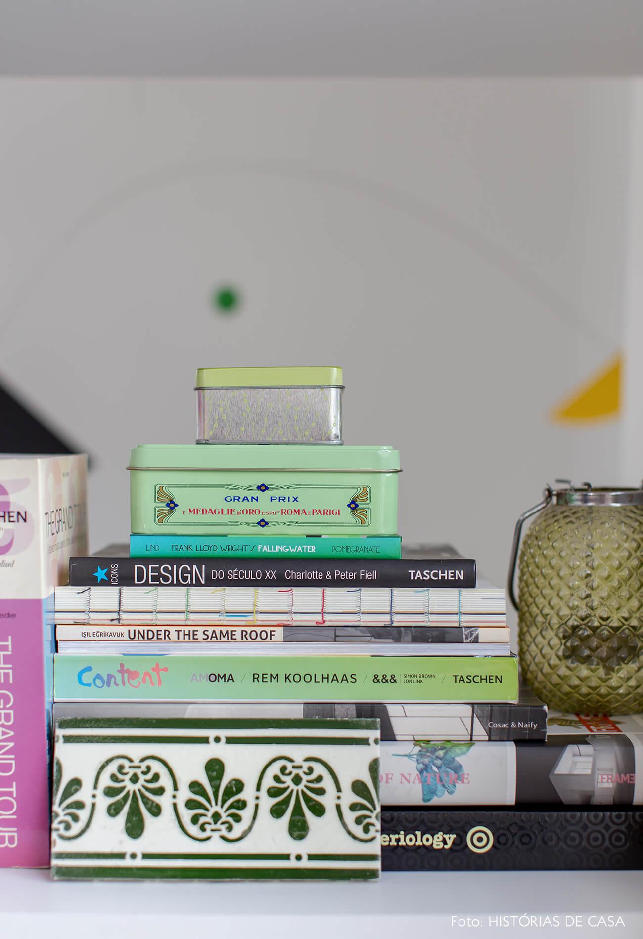 Home office com estante branca e livros separados por cor