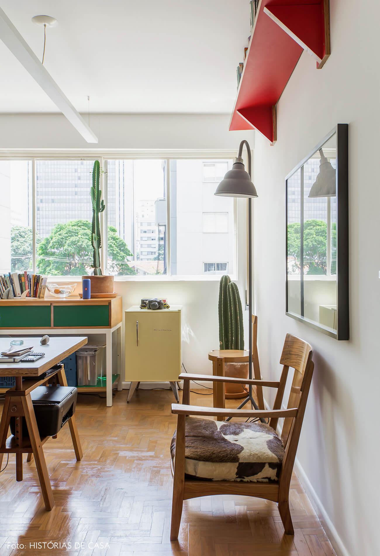 Home office com frigobar amarelo e muitas plantas e cactos